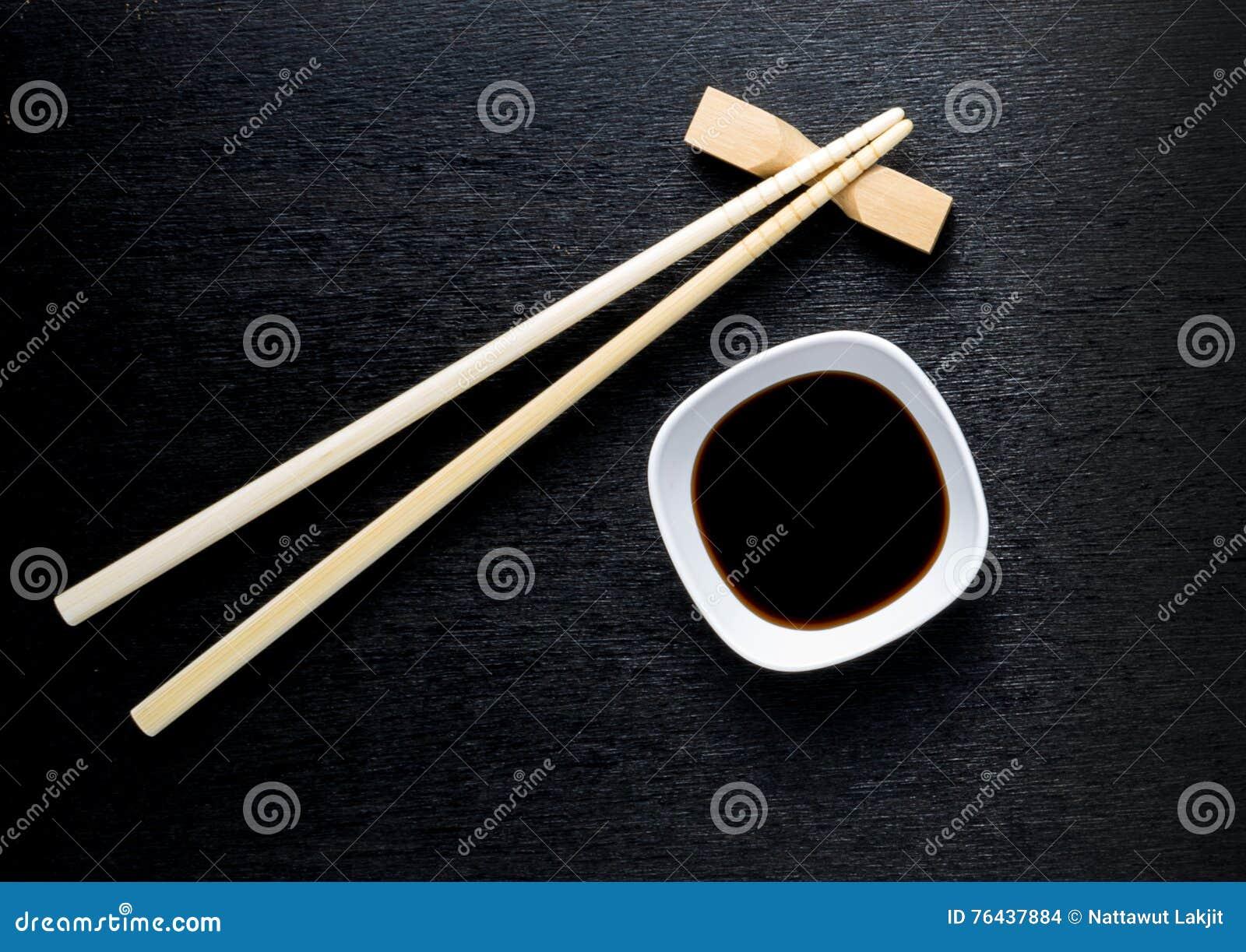 Japońscy suszi chopsticks nad soja kumberlandem rzucają kulą, ryż na czarnym bac