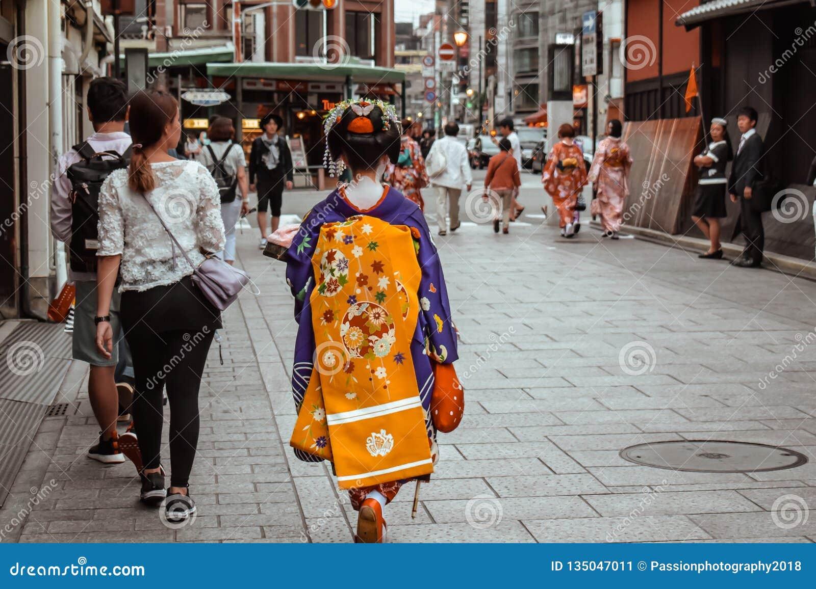 Japońska gejsza w błękitnym i żółtym kimonowym odprowadzenie puszku ulica w Gion Kyoto Japonia