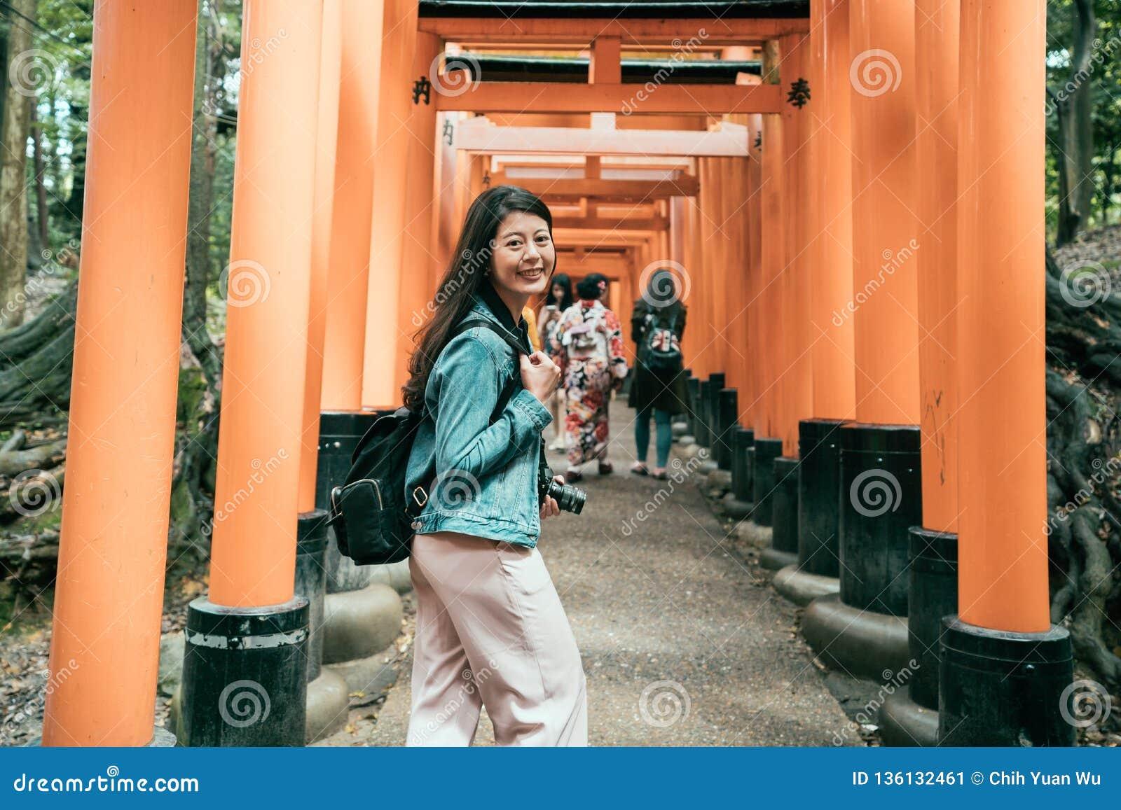 Japońskie damy w kimonowym odprowadzeniu pod torii