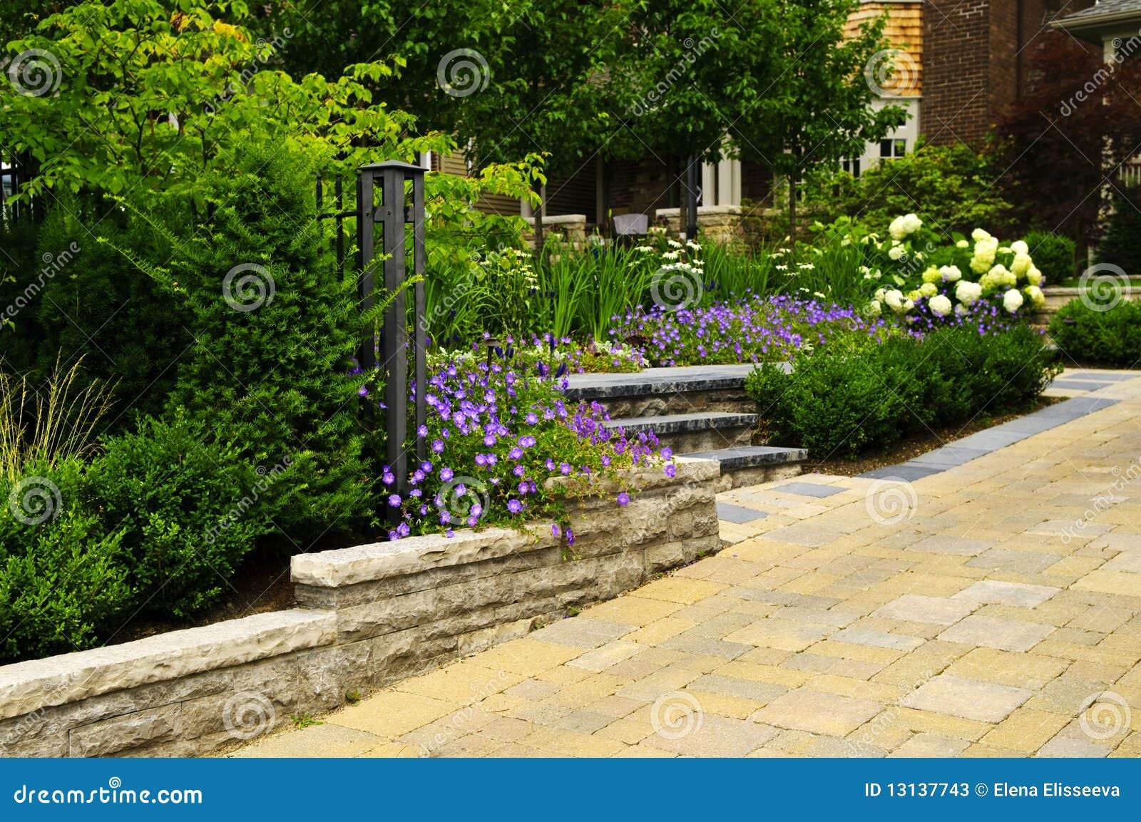 Jardín ajardinado y calzada pavimentada piedra