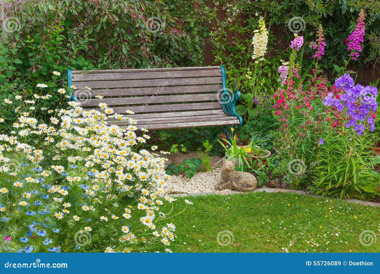 Jard n con las flores del verano y el banco de madera foto for Banco para jardin