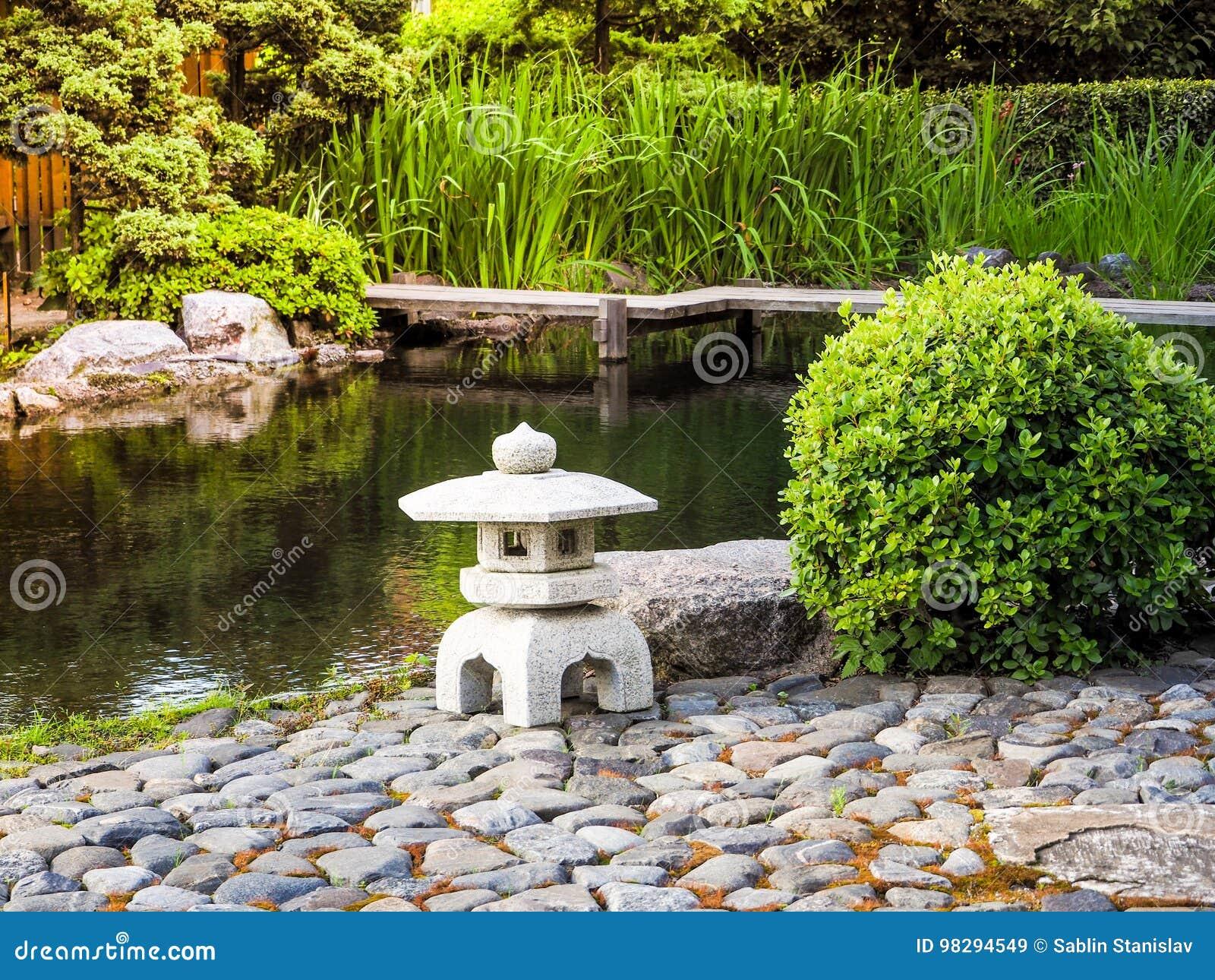 Jard n japon s linterna de piedra colocada entre las for Plantas jardin japones