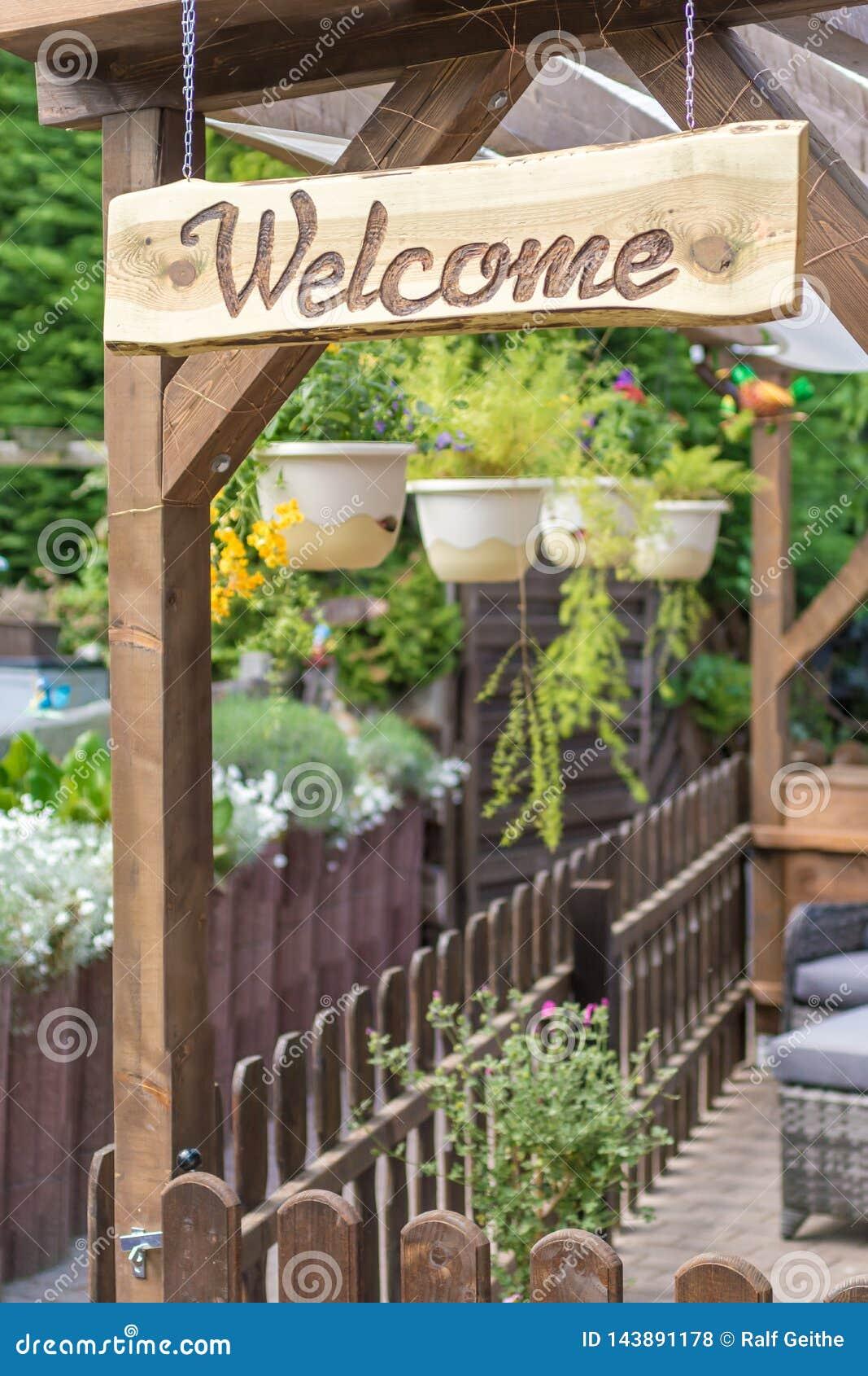 Jardim acolhedor e convidando com muitos plantas e sinal bem-vindo