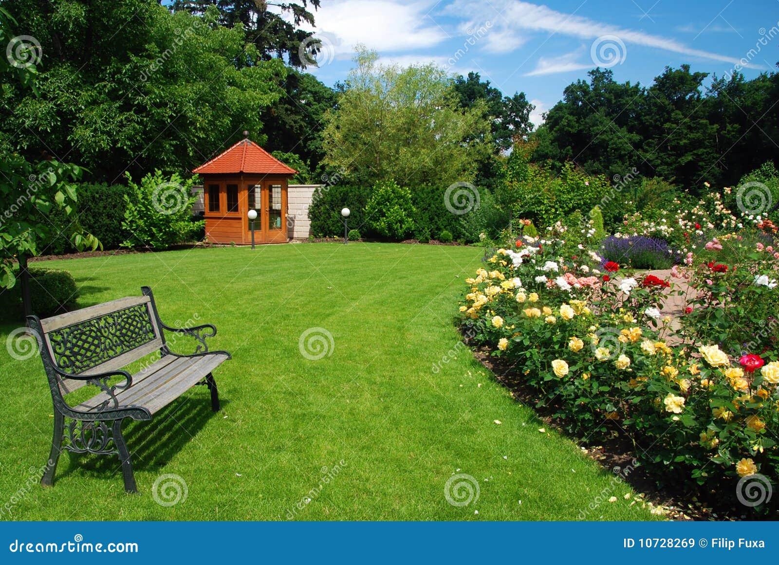 imagens jardim de rosas:Jardim bonito com rosas de florescência, trajeto do tijolo, banco e