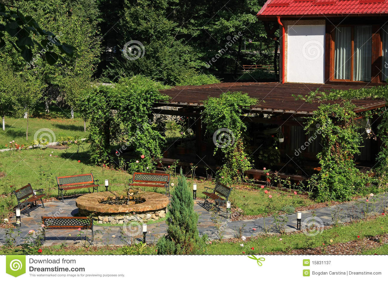 jardim quintal grande:Jardim grande com bancos, fonte e lotes do verde.