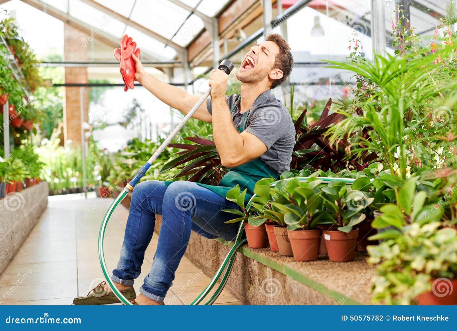 Jardinero feliz que canta en invernadero