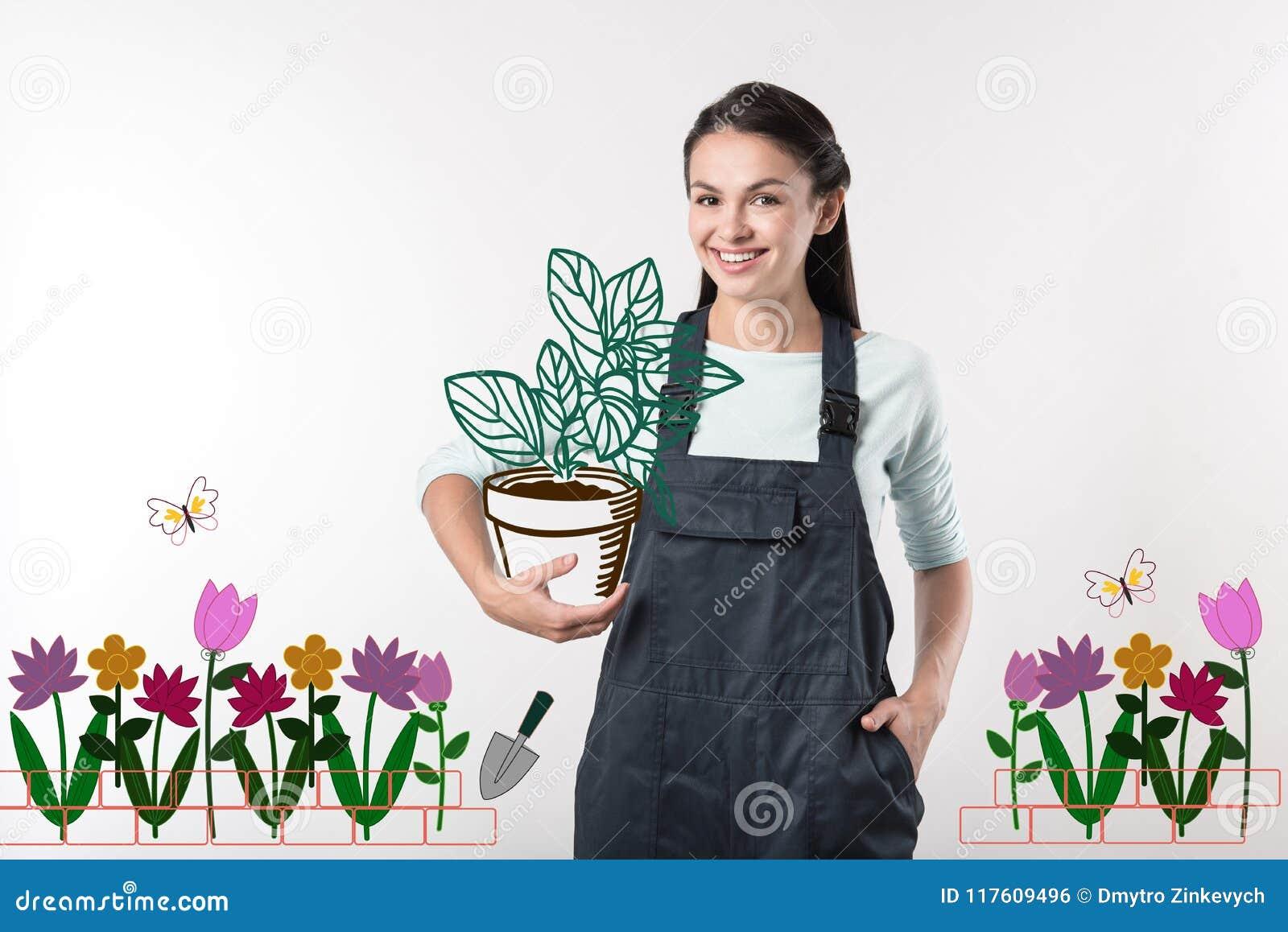 Jardinero positivo que parece alegre mientras que sostiene una planta grande