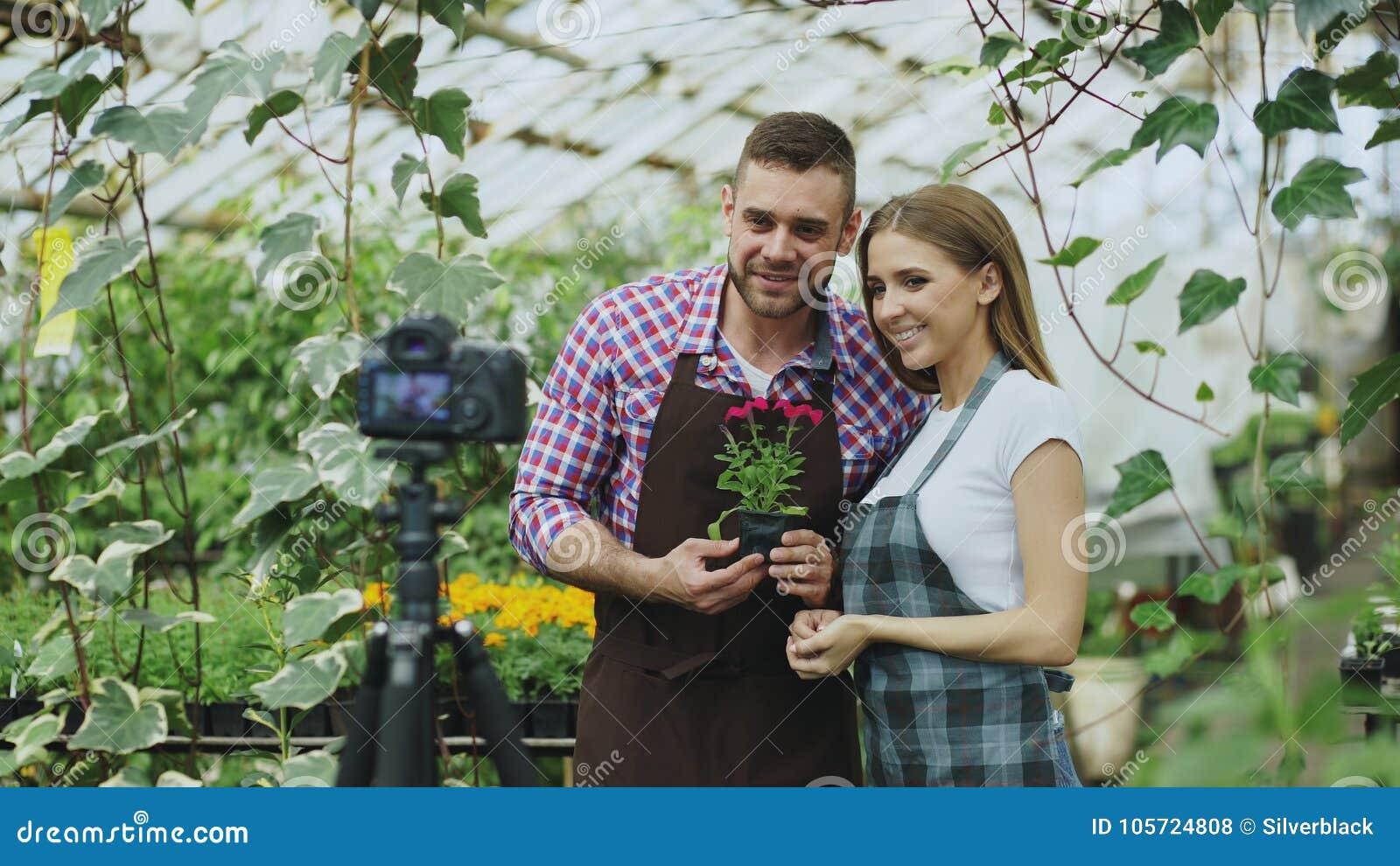 Jardineros sonrientes jovenes de los pares del blogger en el delantal que sostiene la flor que hablan y blog video de registració