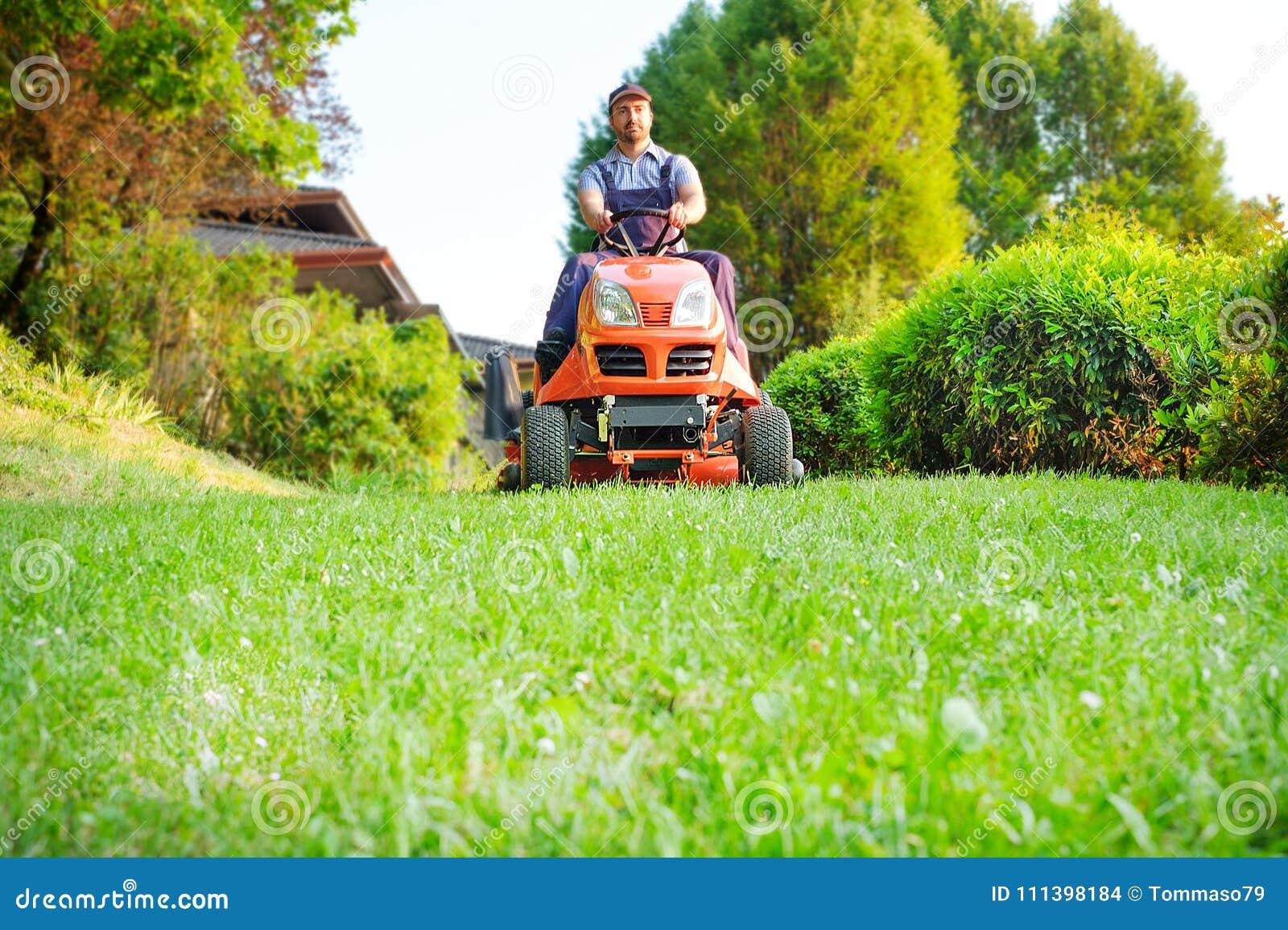 Jardinier conduisant une tondeuse à gazon d équitation dans le jardin