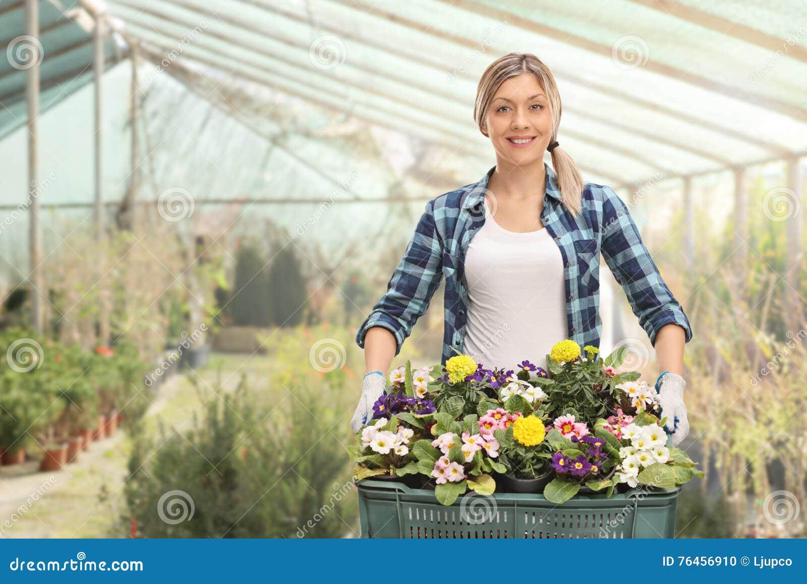 Jardinier féminin tenant un support des fleurs