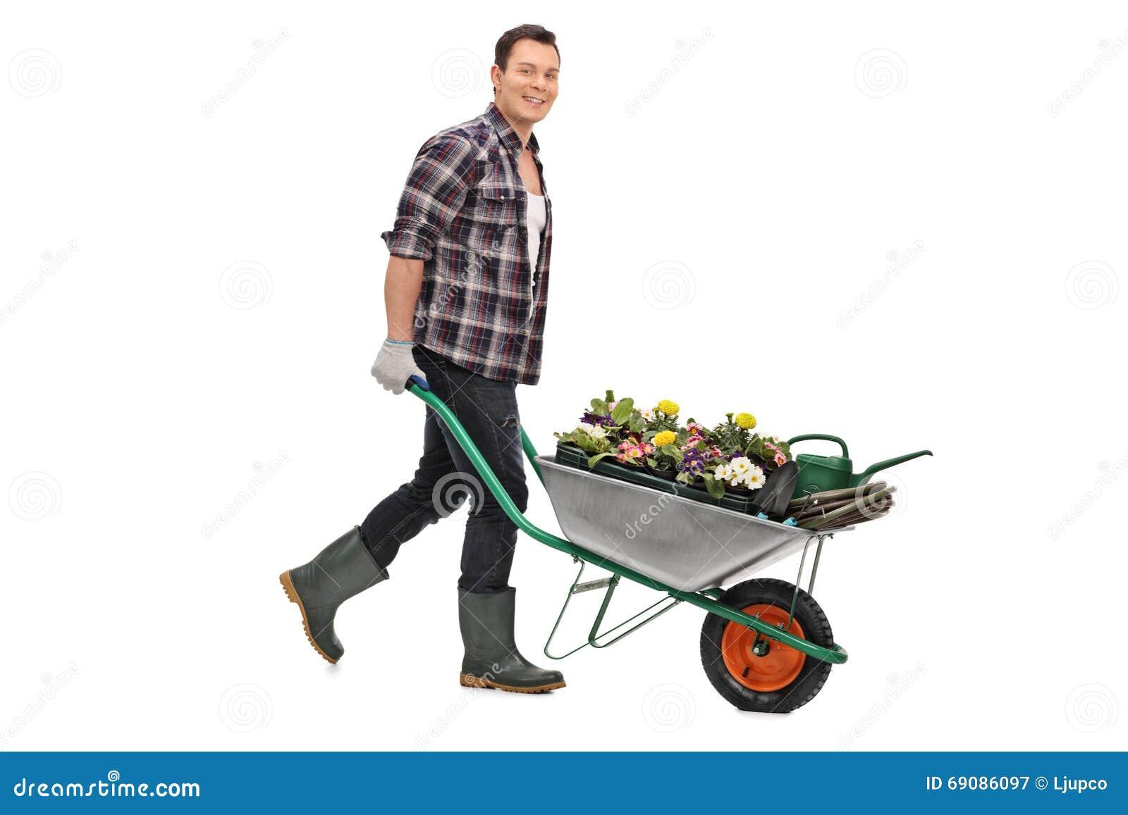 Jardinier poussant une brouette avec des fleurs