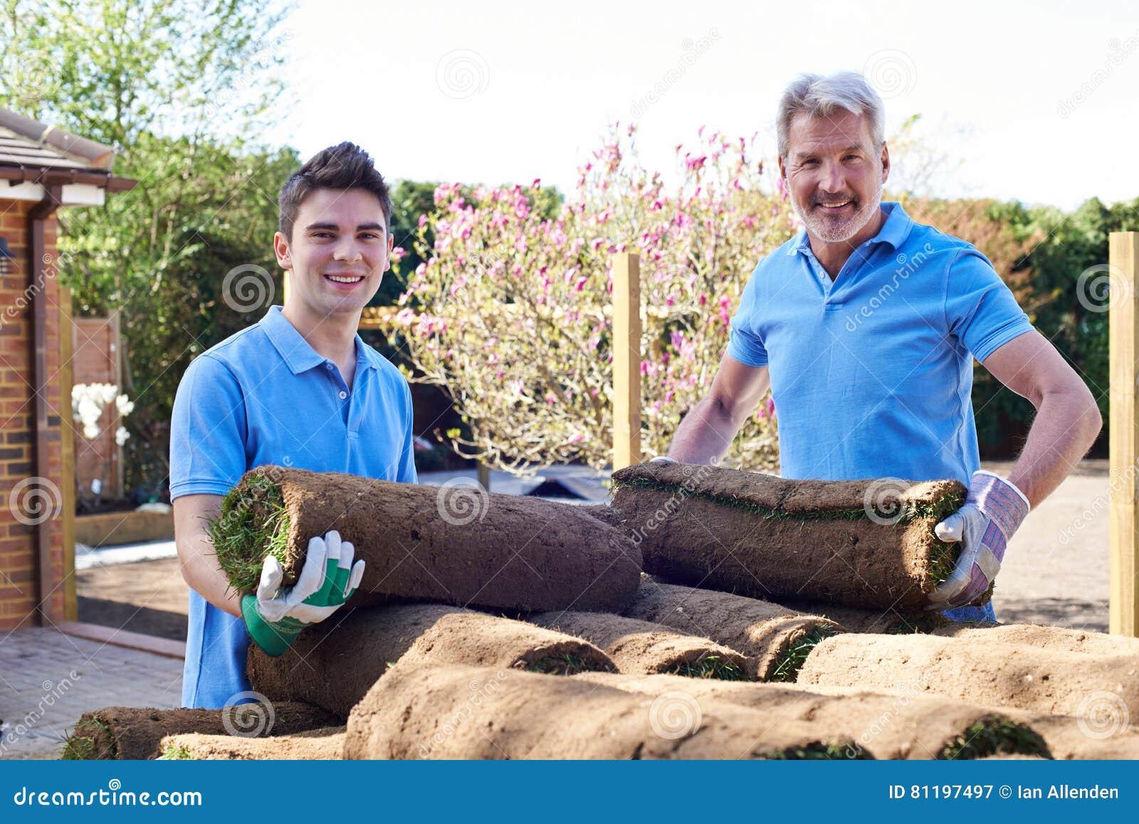 Jardiniers de paysage étendant le gazon pour la nouvelle pelouse