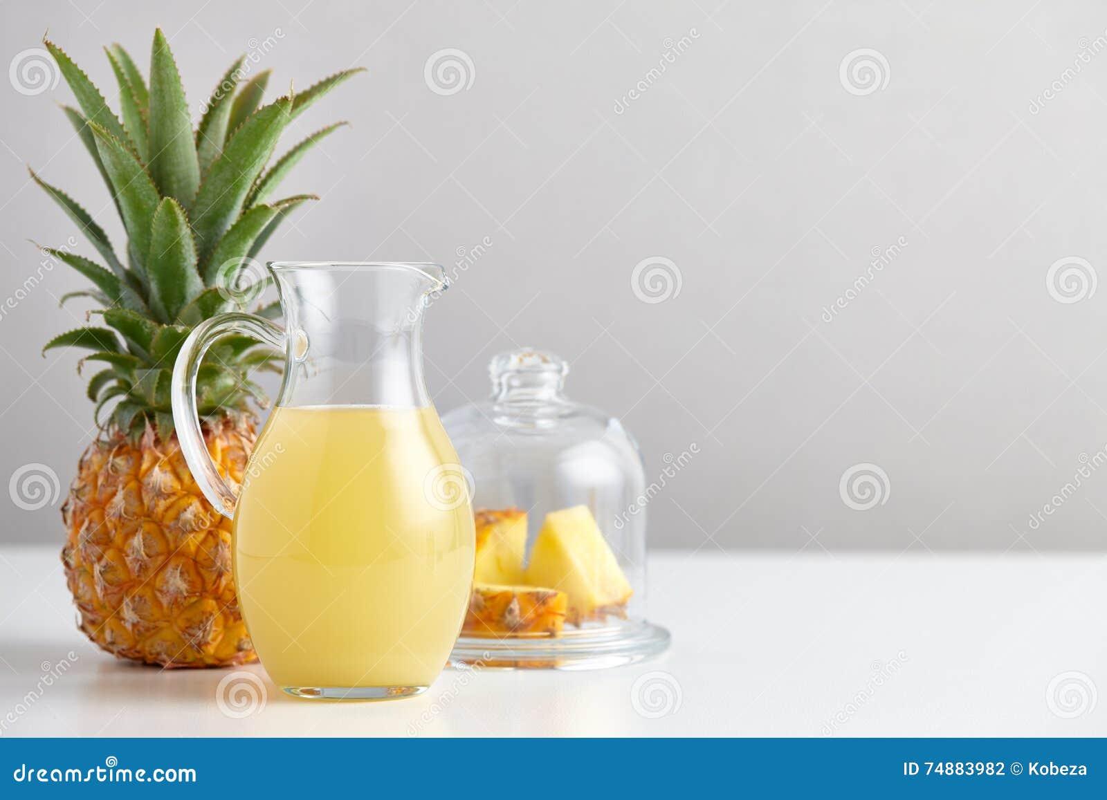 Jarro de vidro com suco e fruto de abacaxi na tabela