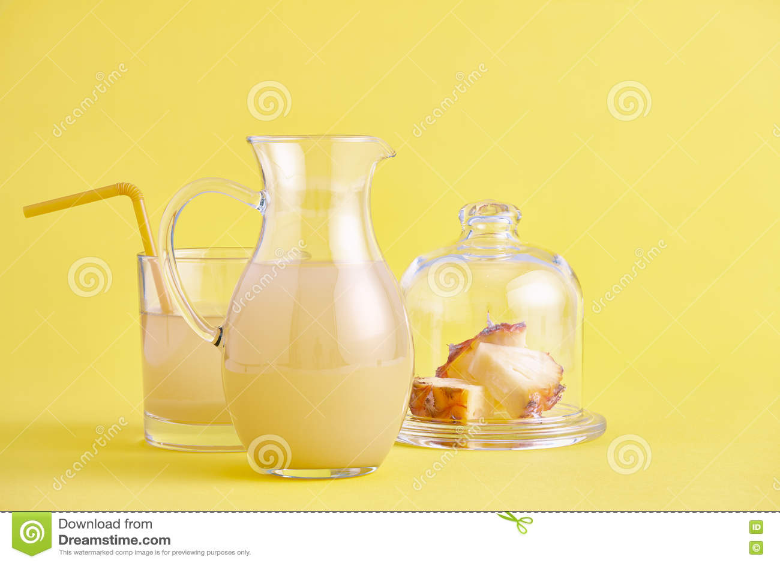 Jarro de vidro de suco de abacaxi fresco no amarelo