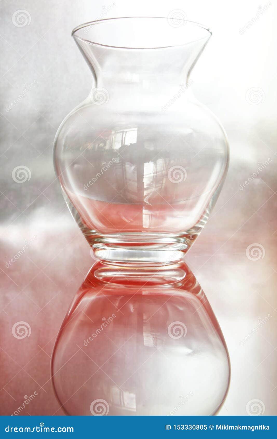 Jarro de vidro transparente em um fundo cor-de-rosa de prata Um exemplo para um esboço em uma lição de tiragem em uma escola de a