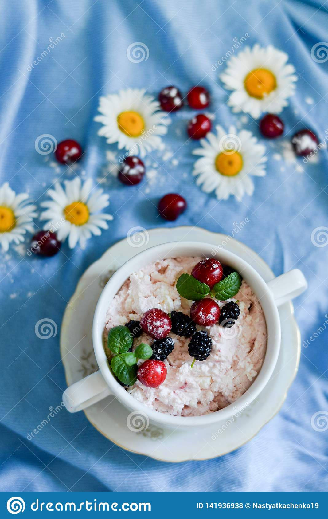 Jars of natural white yogurt with fruit salad with pink dragon fruit, berries and mint on table. Healthy eating. Copy space.blue
