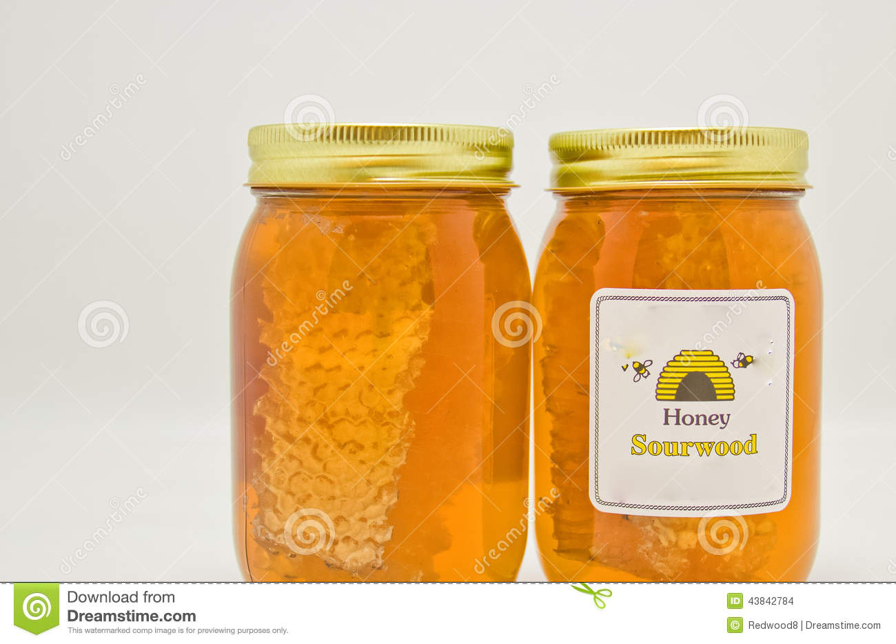 Sour wood honey in clear glass jars along with honeycomb.