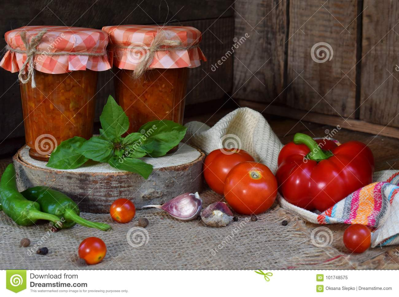 Jars of tomato sauce with chili, pepper and garlic. Bolognese sauce, lecho or adjika. Preservation. Canning.