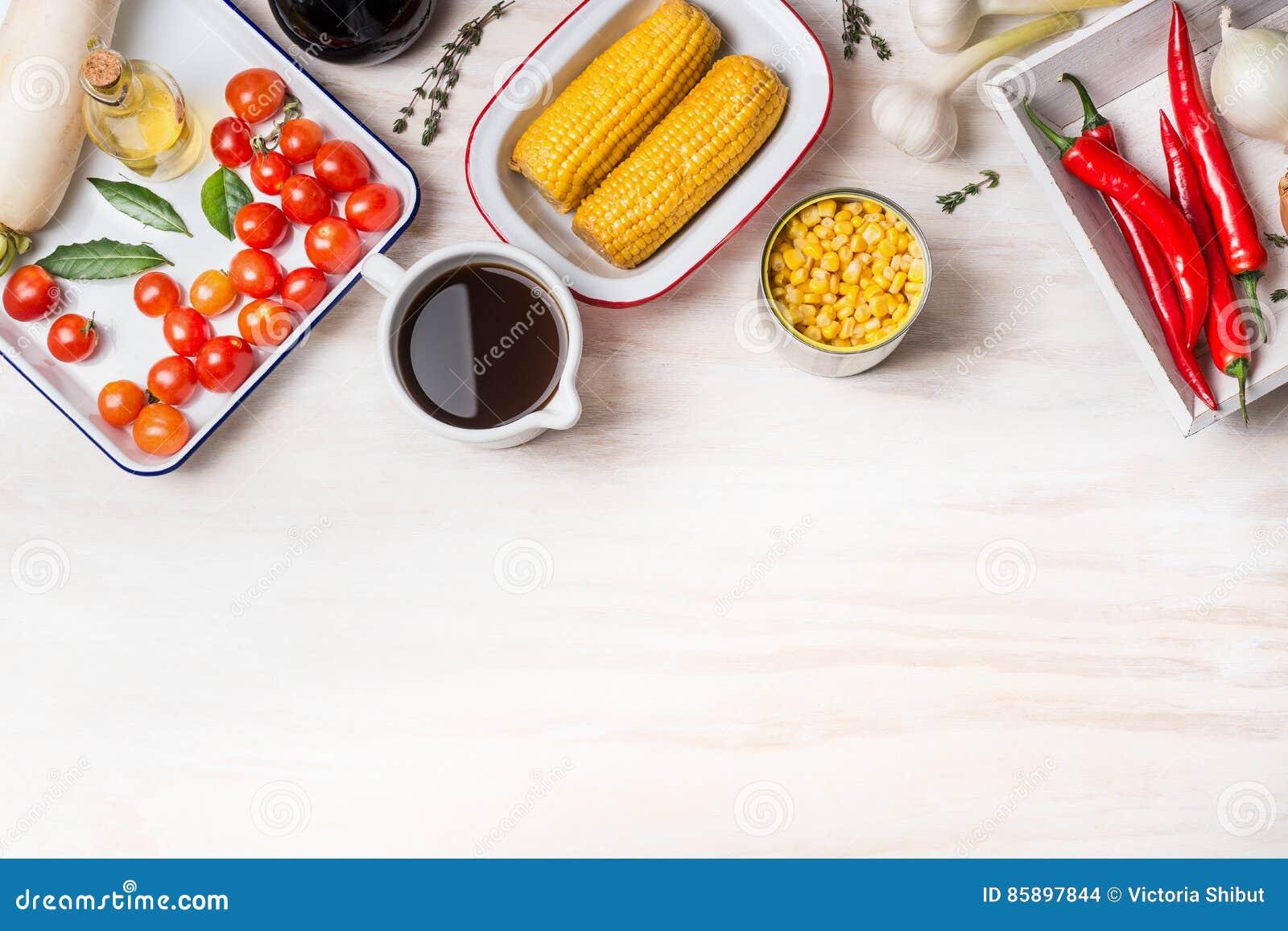Jarski kukurydzany zupny przygotowanie z różnorodną kukurudzą, rosołem i kulinarnymi składnikami na białym drewnianym tle, odgórn