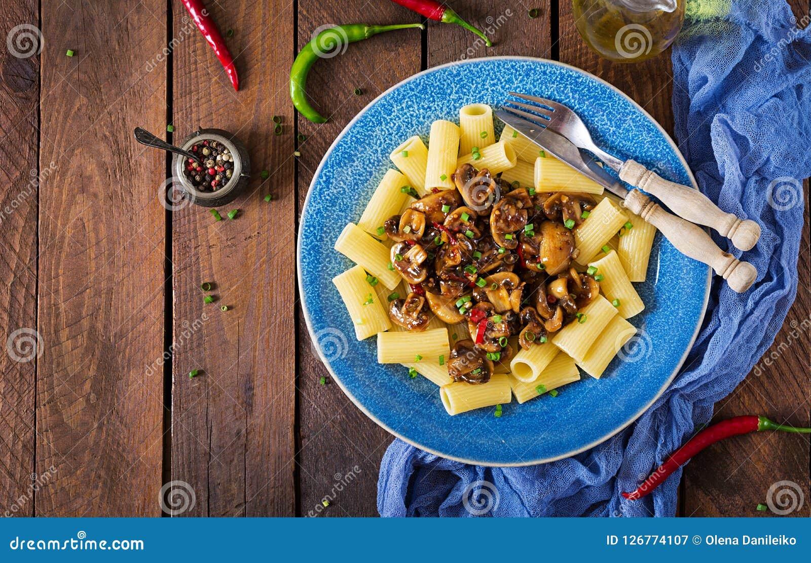 Jarski makaronu rigatoni z pieczarkami i chili pieprzami w błękitnym pucharze