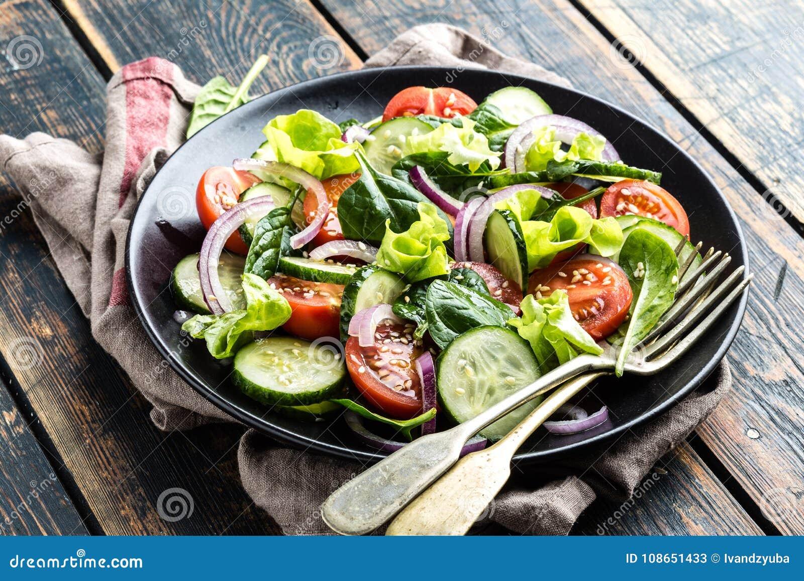 Jarzynowa sałatka świeży pomidor, ogórek, szpinak, cebula i sałata na talerzu,
