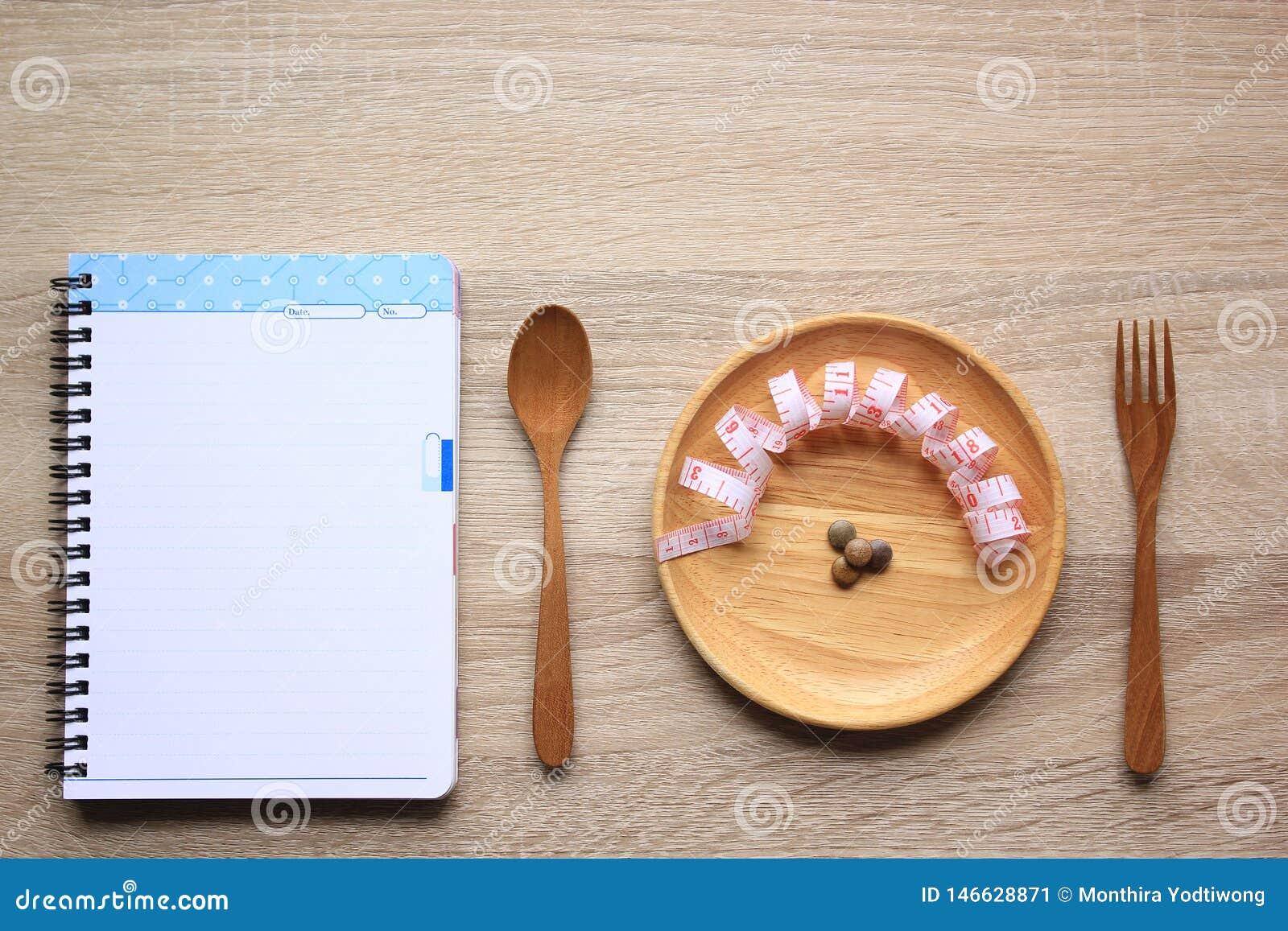 Jarzynowi wyrka i miara taśmy drewnem, puste miejsce notatnika łyżki i rozwidlenia i, stroną, Zdrowym łasowanie i dieta w drewnia