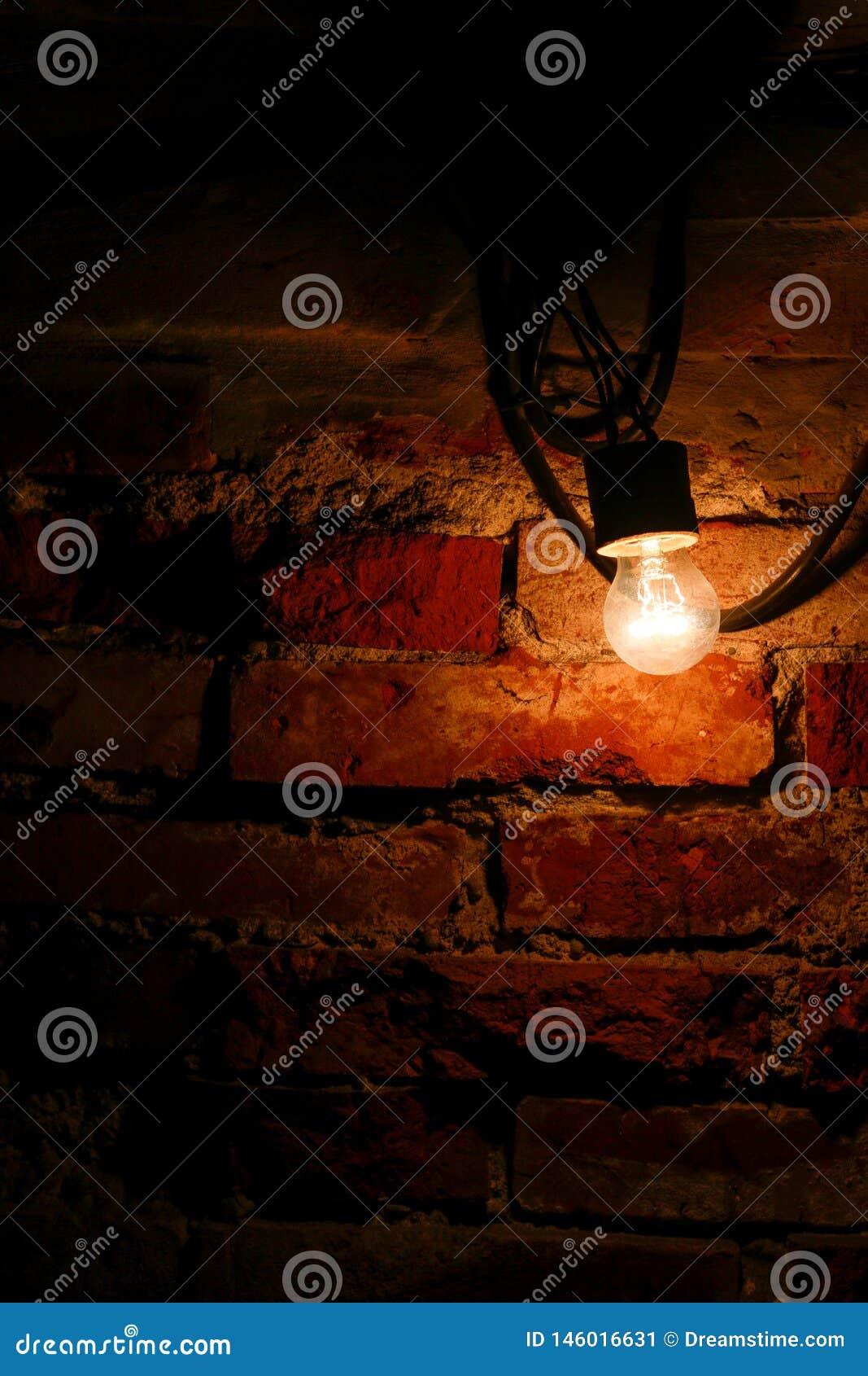 Jaskrawa żarówka obok starej ściany z cegieł