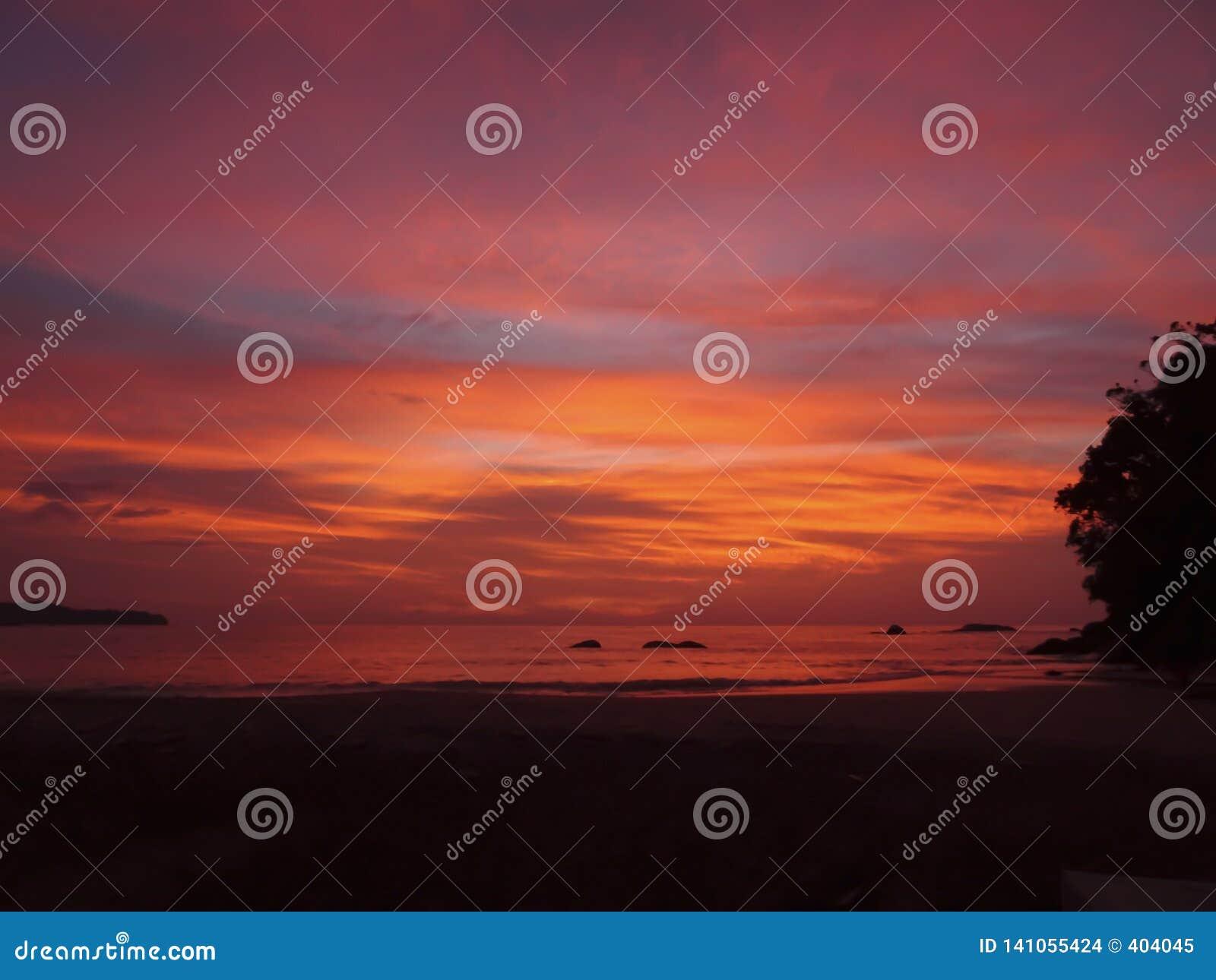 Jaskrawa pomarańcze, menchia, purpurowy zmierzch barwi nad spokojnym morzem