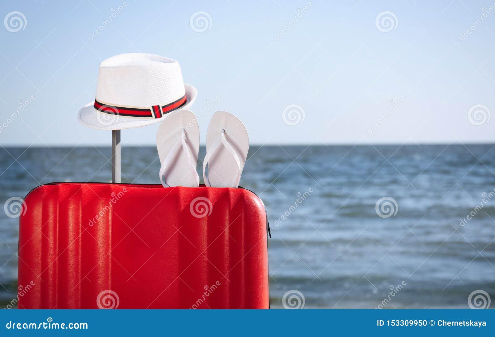 Jaskrawa walizka i różni plażowi akcesoria na piasku blisko morza