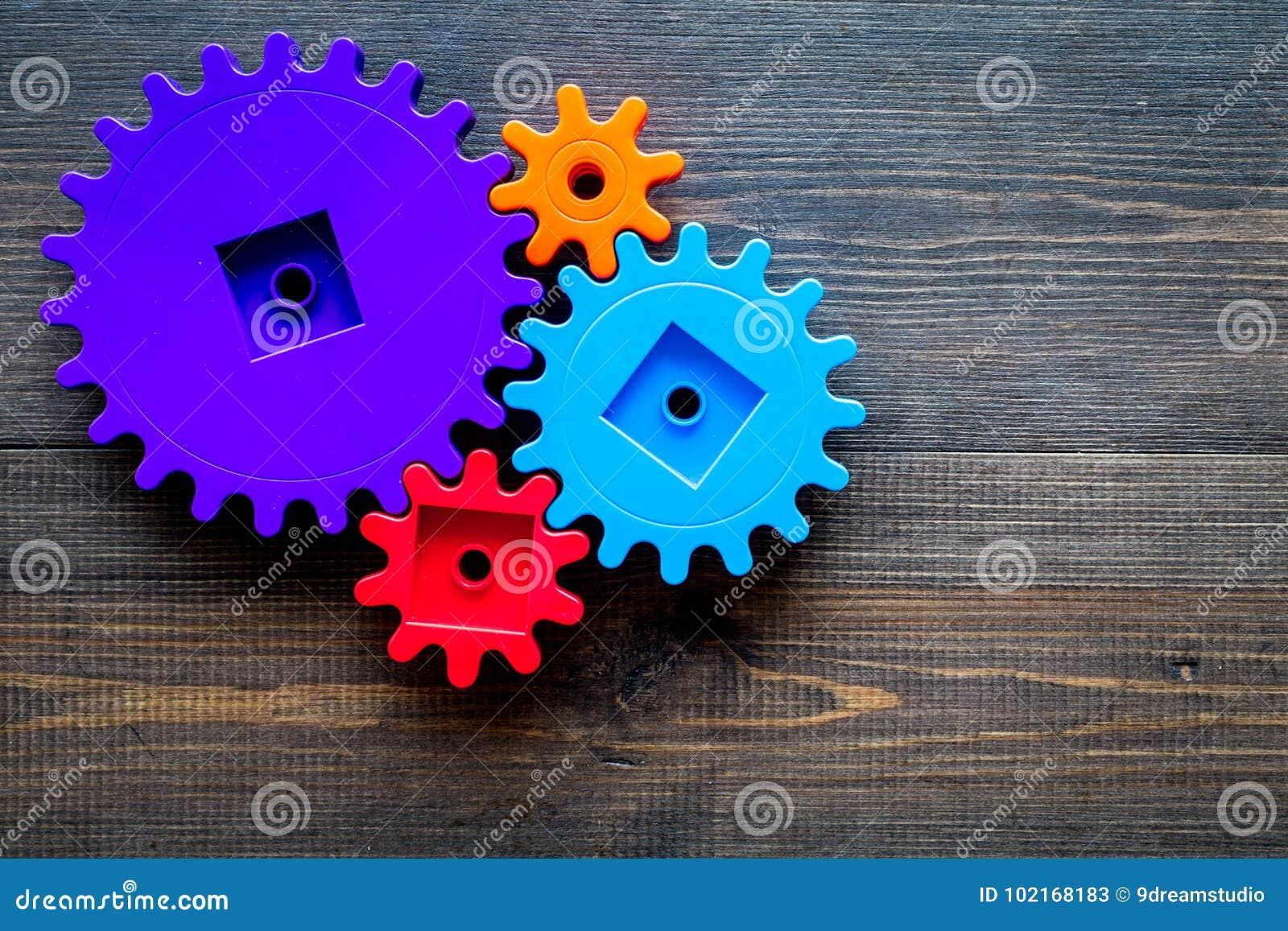 Jaskrawe przekładnie dla wielkiej technologii drużynowa praca i poprawny mechanizm na drewnianym tło odgórnego widoku copyspace