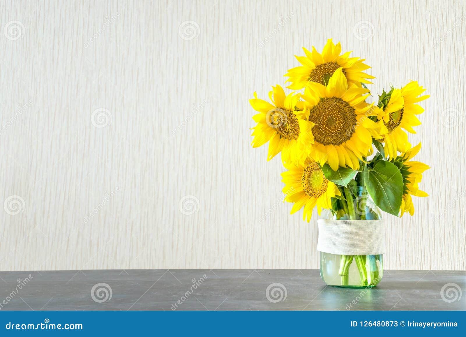Jaskrawi żółci duzi słoneczniki w szklanej wazie na zmroku stole na ligh