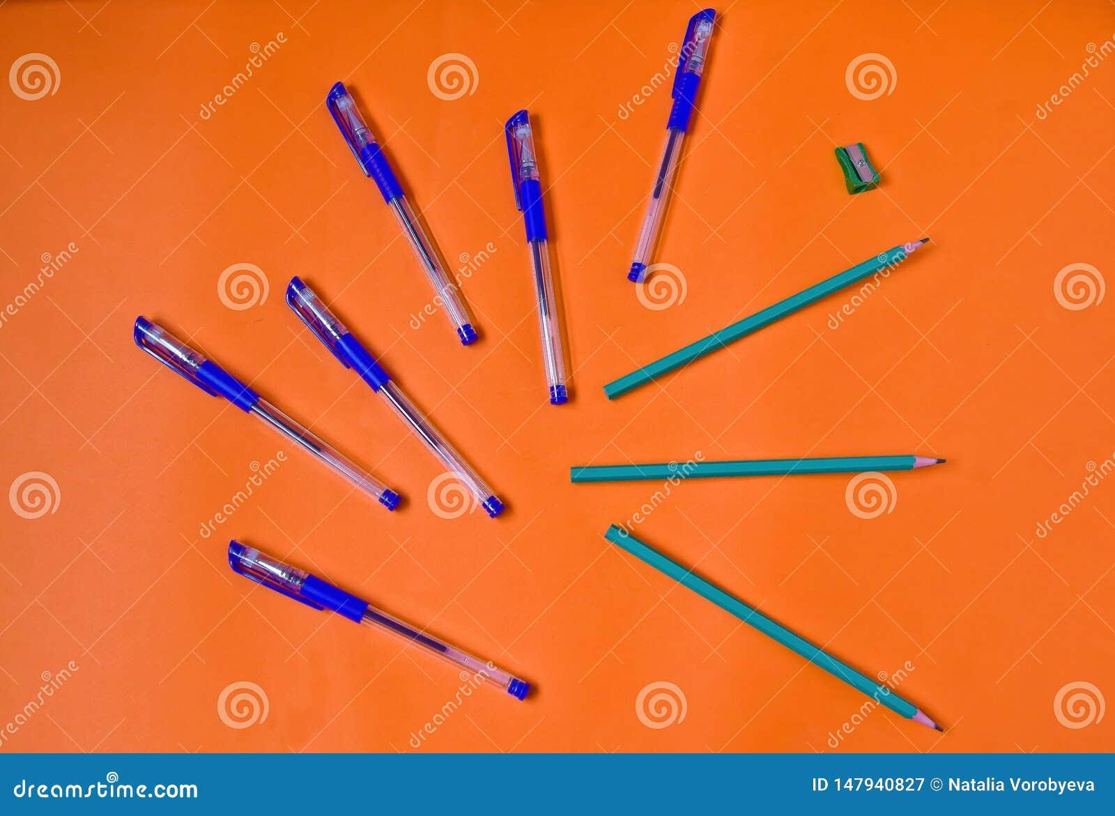 Jaskrawi ołówki na pomarańczowym tle i pióra