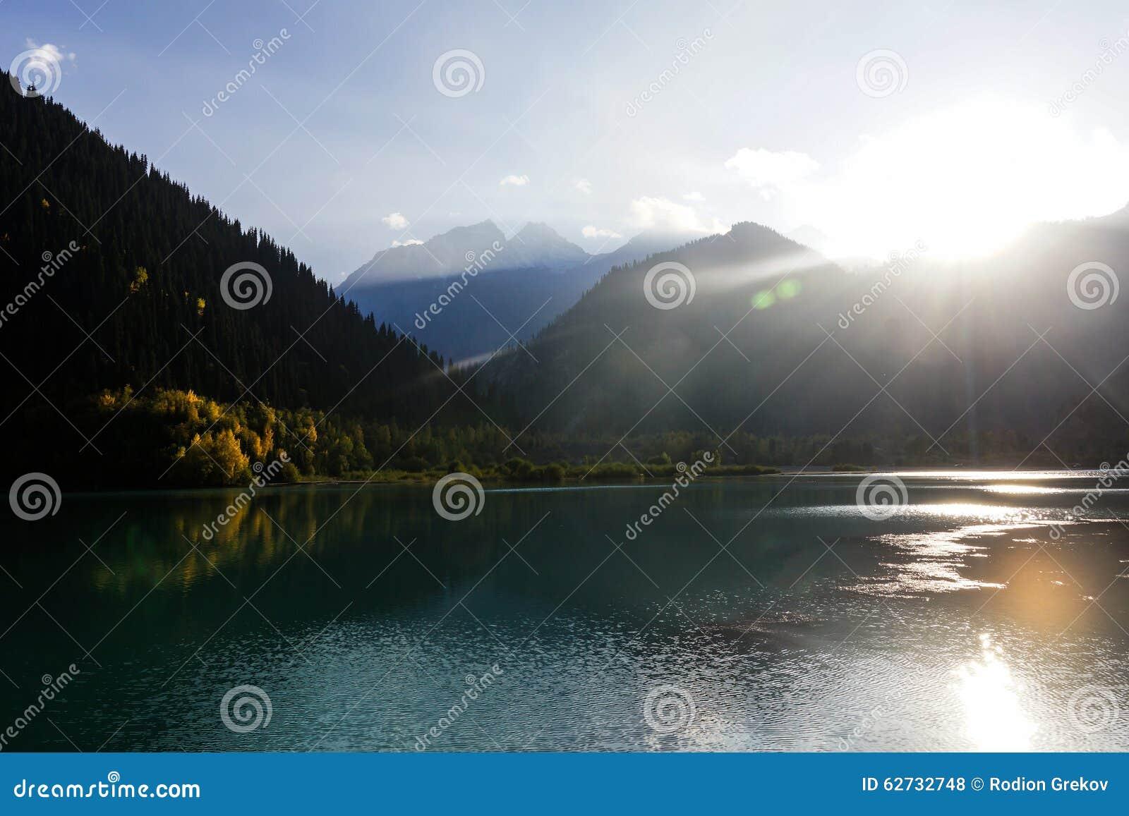 Jaskrawi słońce promienie nad halnym jeziorem