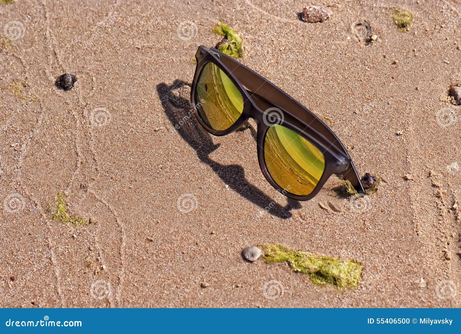 Jaskrawi złociści kolorów okulary przeciwsłoneczni w piasku
