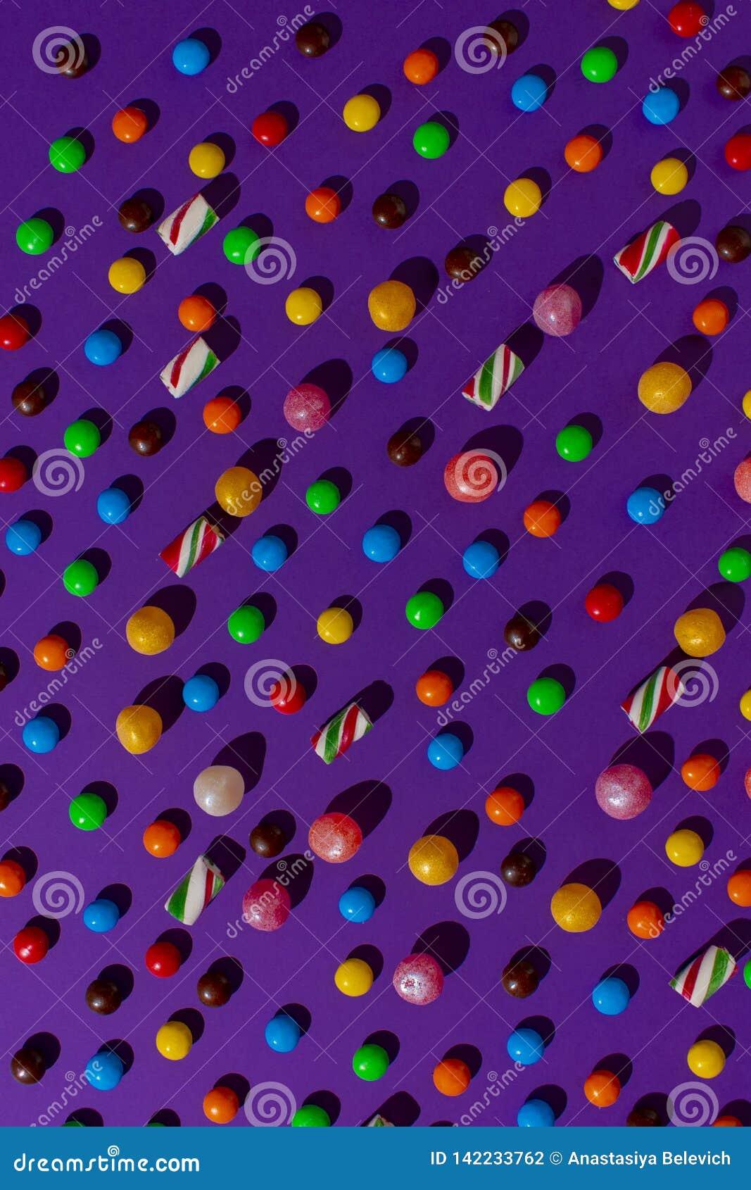 Jaskrawy cukierek rozpraszał na płaskim purpurowym tle na widok