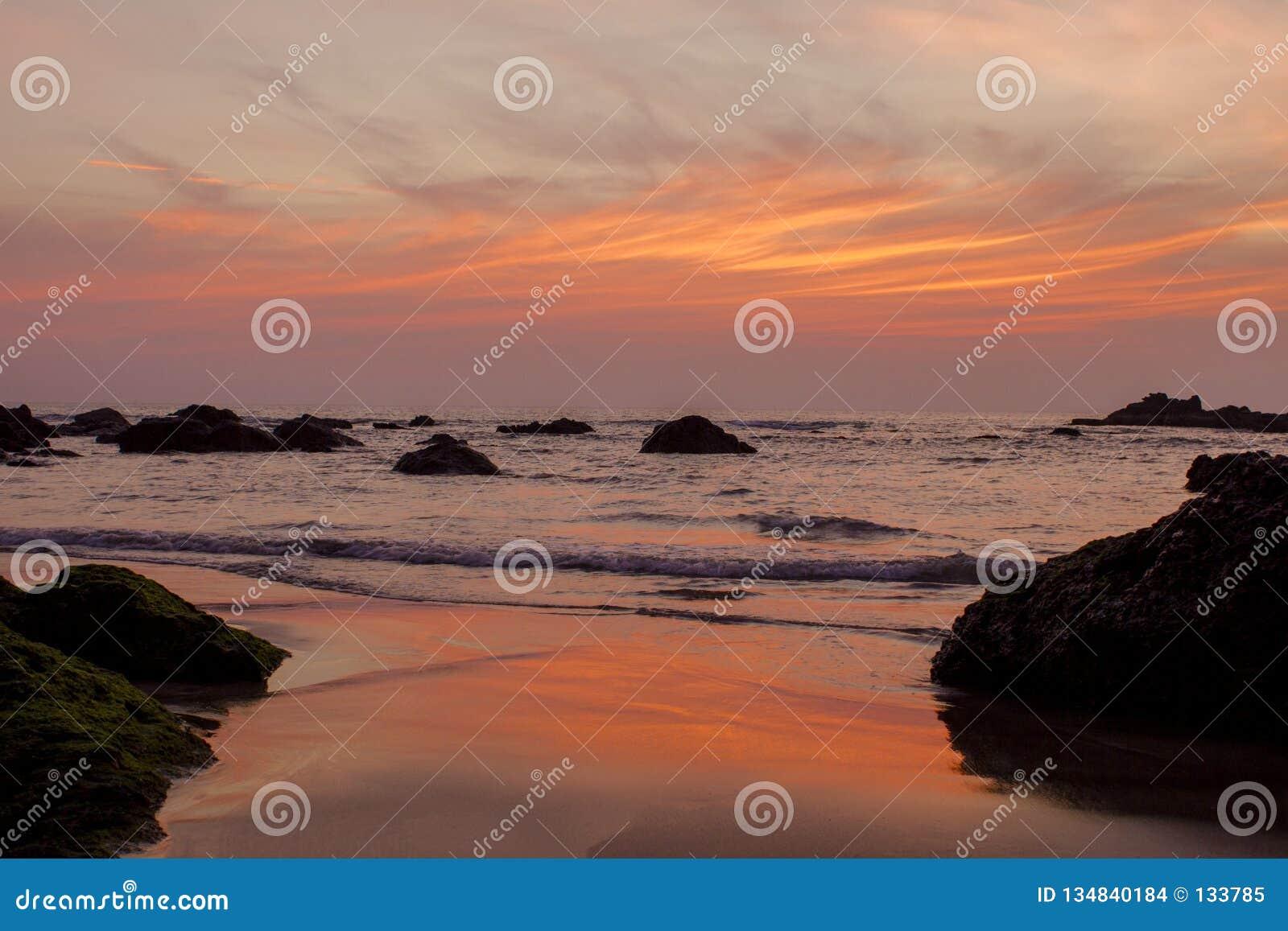 Jaskrawy pomarańczowa błękitnych szarość purpur chmura wykłada w zmierzchu niebie nad morzem z skałami i piaskowatą plażą