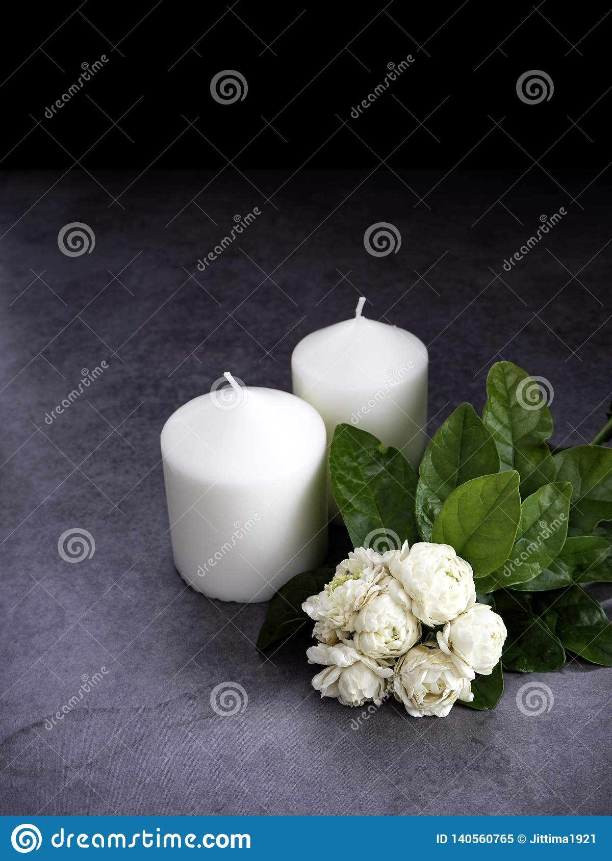 Jasmine and candles on dark background