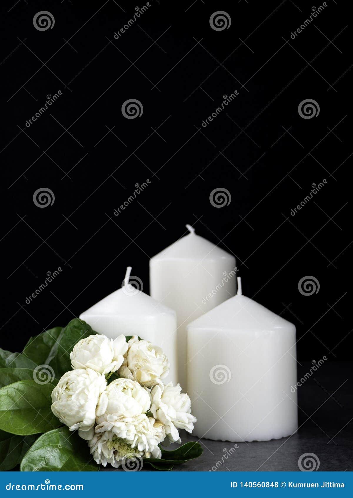 Jasmine and candles on dark background