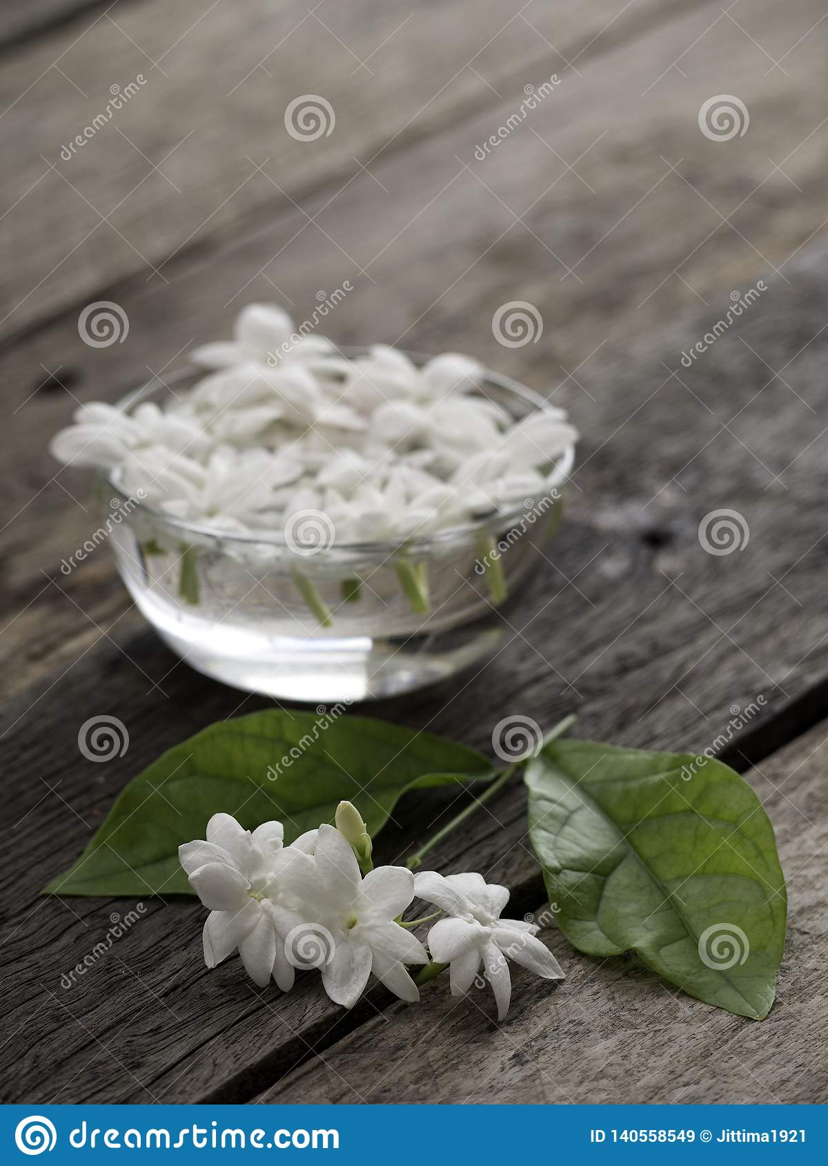 Jasmine floating in clear glass on wooden background