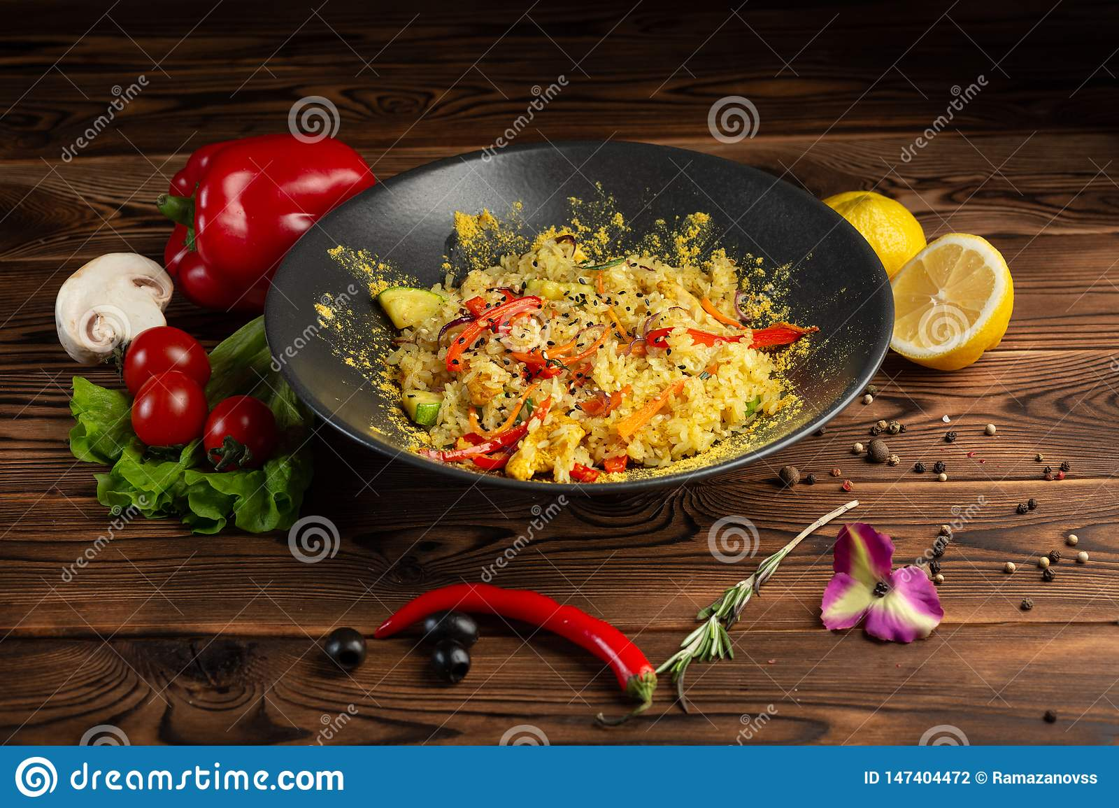 Jasmine rice with chicken in a black plate on wooden background