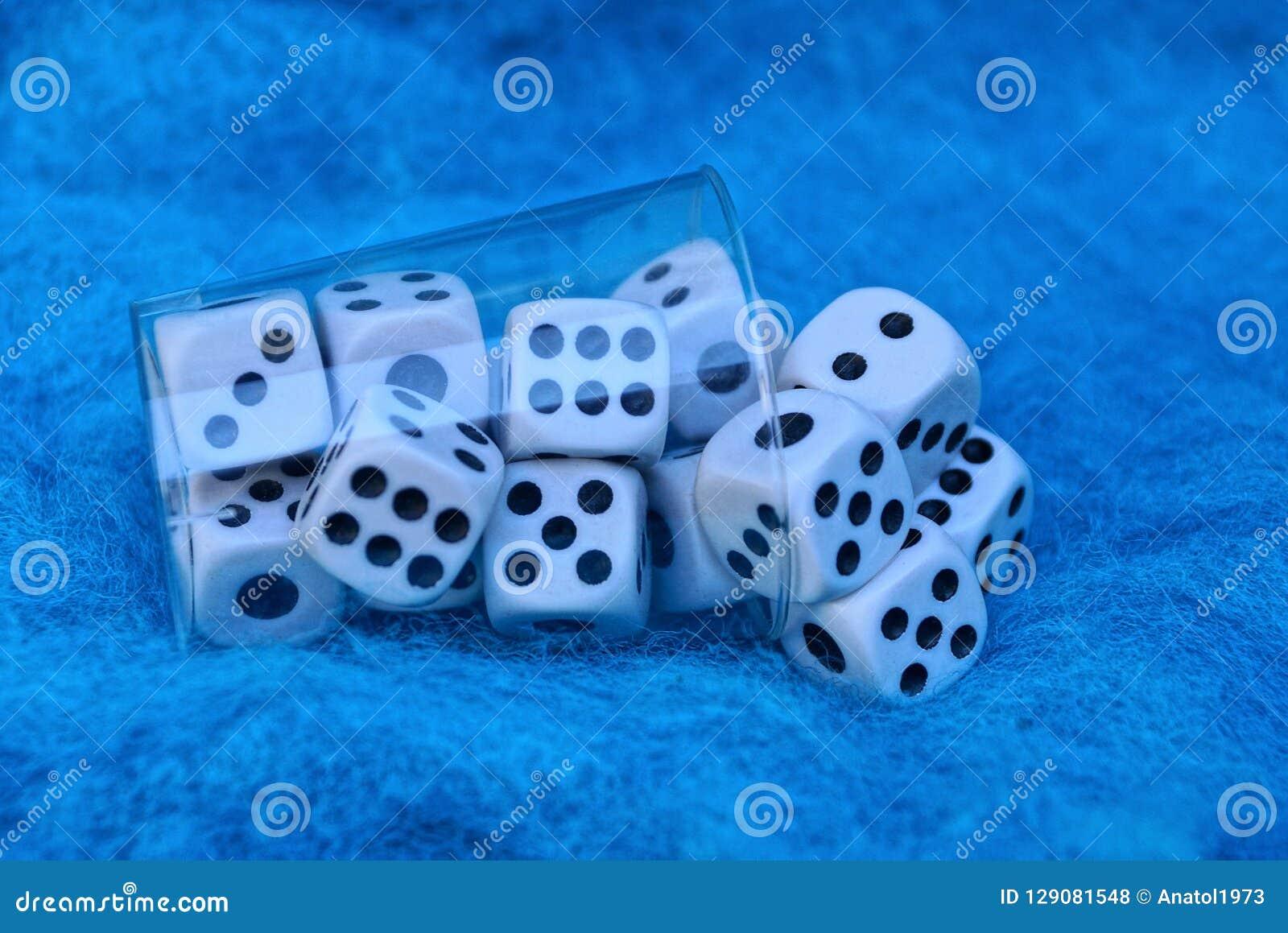 Jasna plastikowa filiżanka z białymi kostkami do gry na błękitnej wełny tkaninie