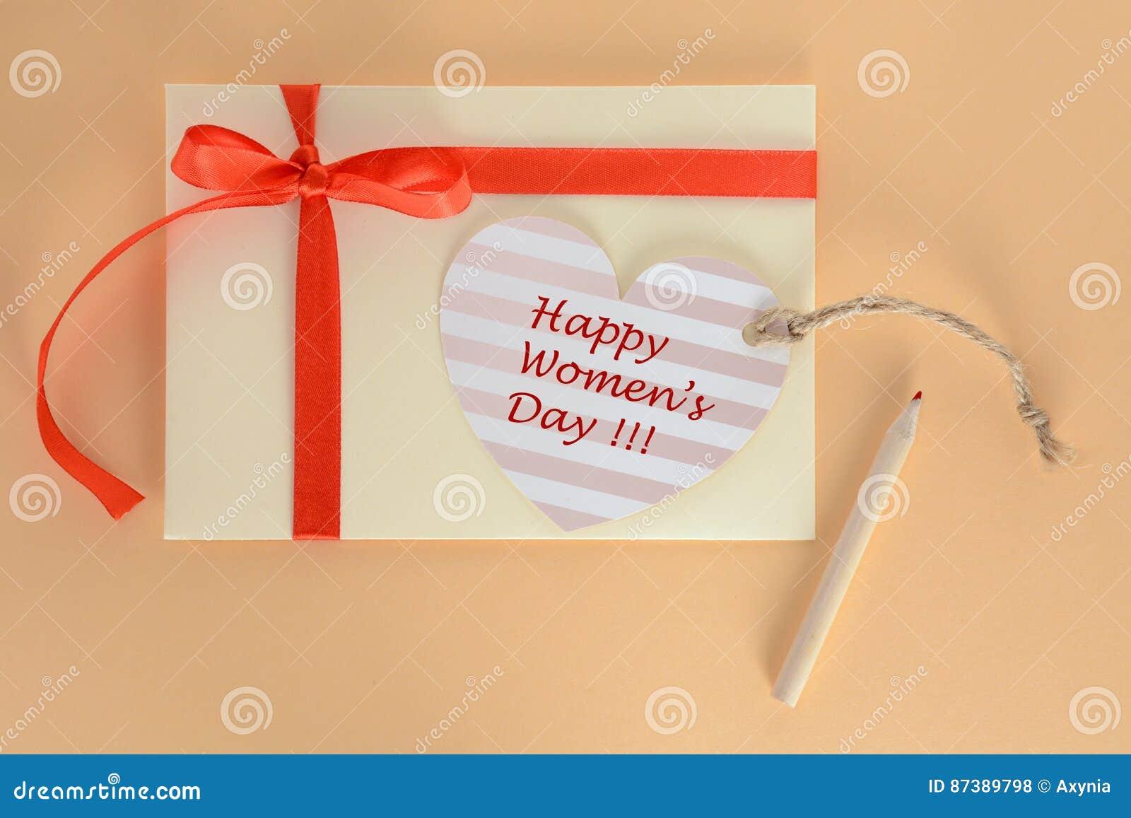 Jasnożółta koperta z czerwonym faborkiem i kierowa Szczęśliwa kobieta dnia karta na morelowym tle