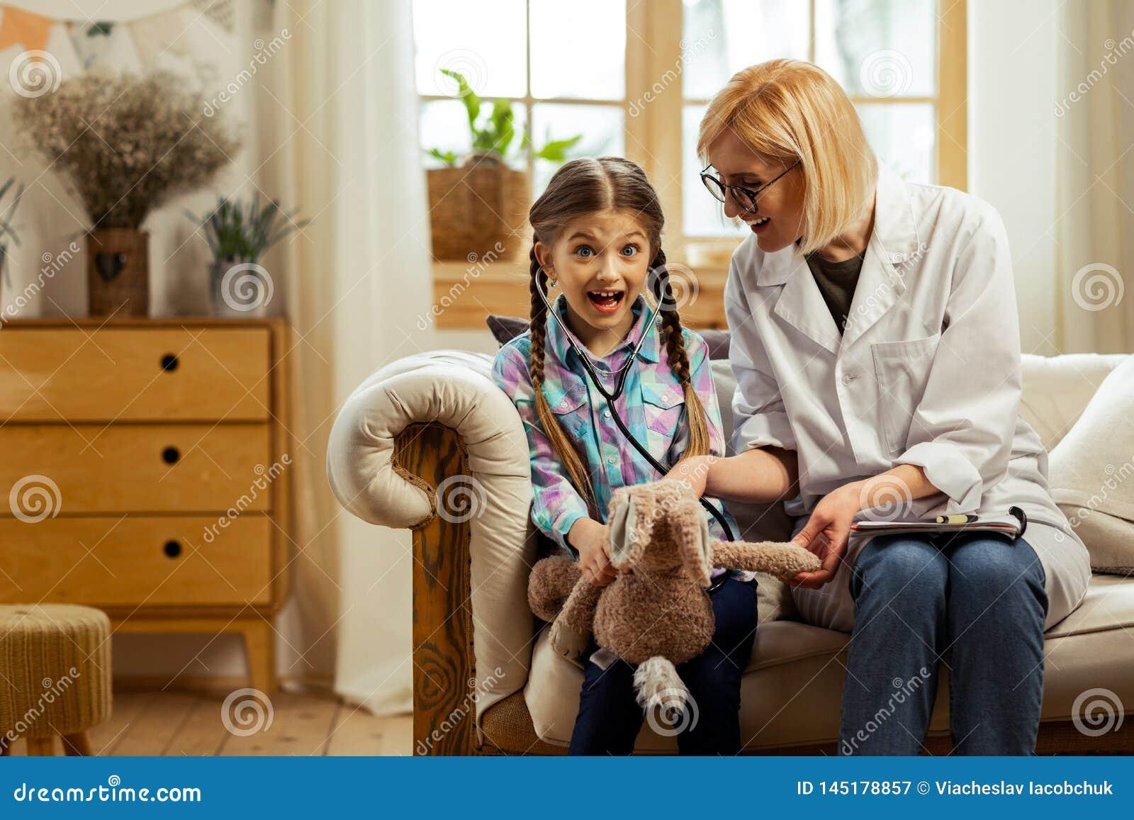 Jasnogłowy pediatra daje dziewczynie stetoskopowi próbować dalej
