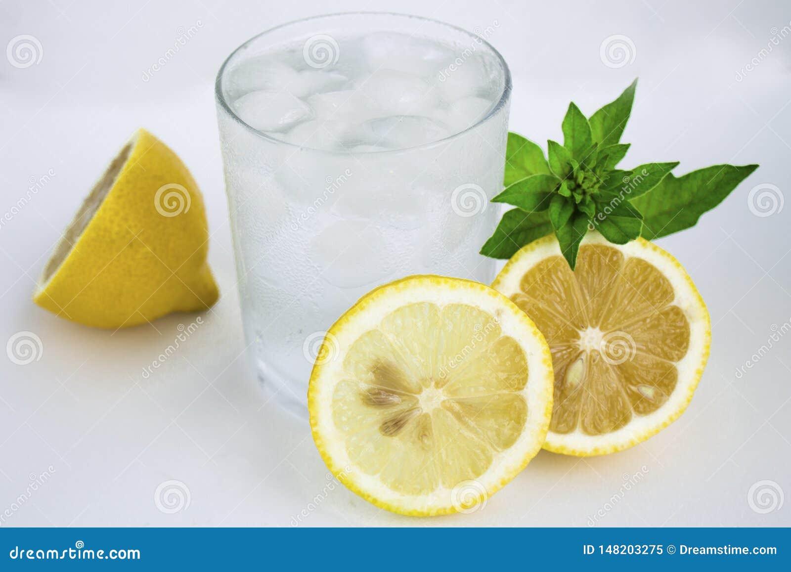 Jasny szkło z zimną wodą, cytryna i mennica