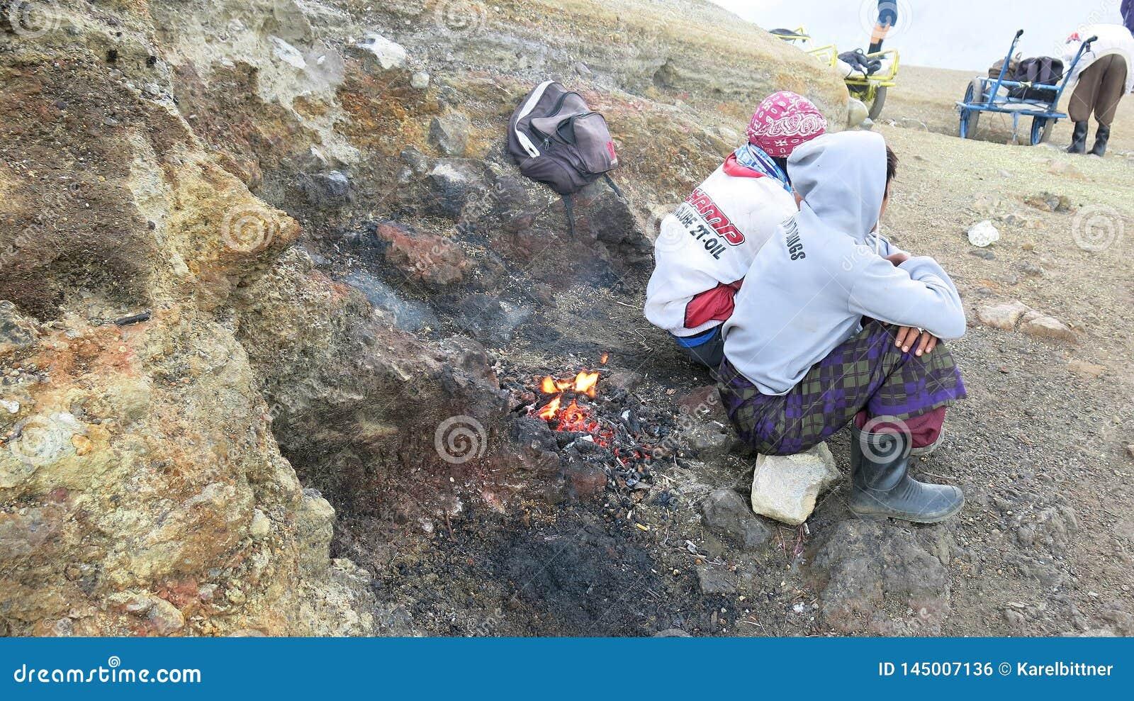 Javanese sulfur miners sitting atop active Kawah Ijen volcano.