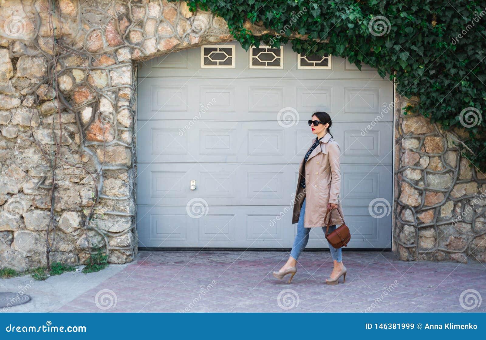 Jeans och dike f?r h?rlig kvinna som b?rande st?r mot v?ggen p? stadsgatan Tillf?lligt mode, elegant daglig blick