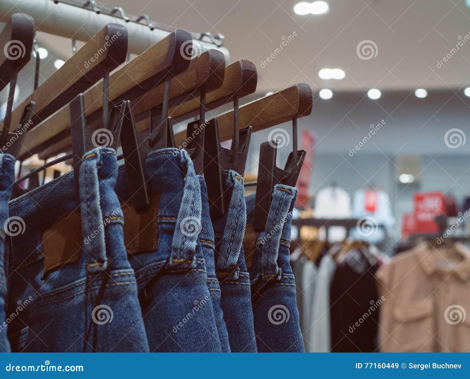Jeans sur des cintres dans le magasin de mode Concept sur les vêtements sport et