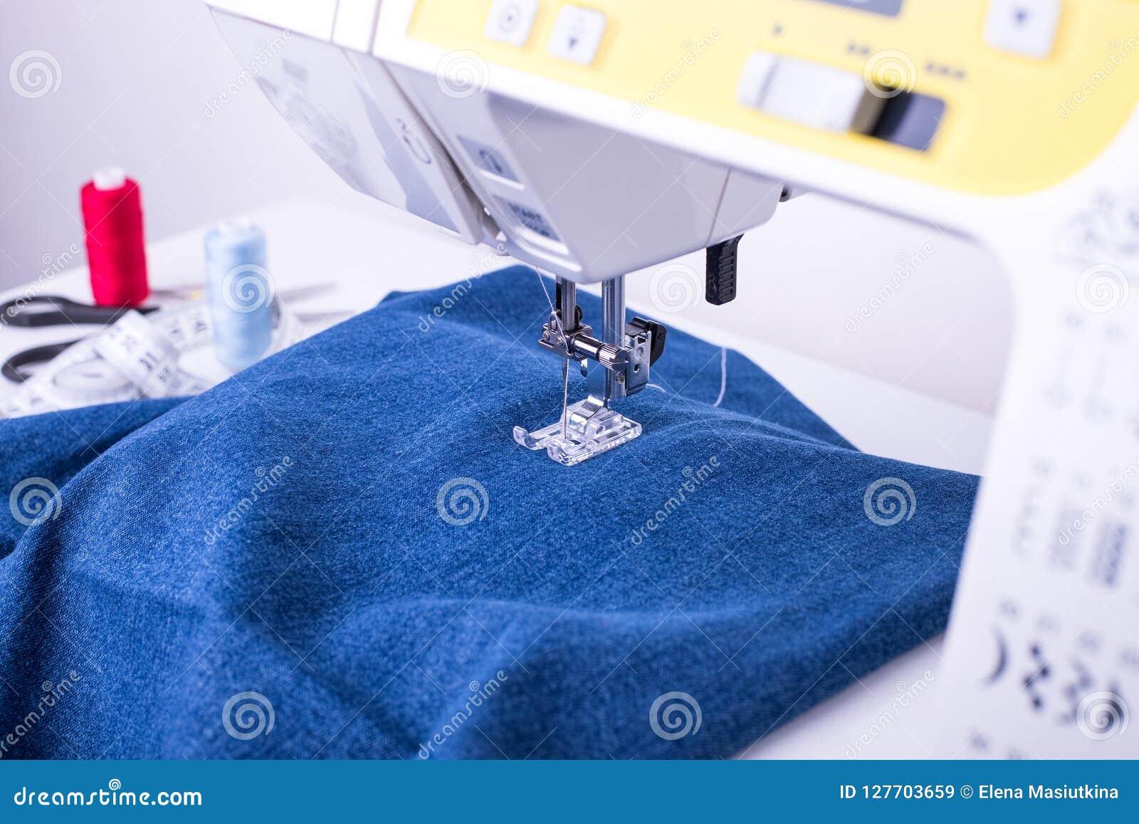 Jeanstyg på symaskinen under sydd fot