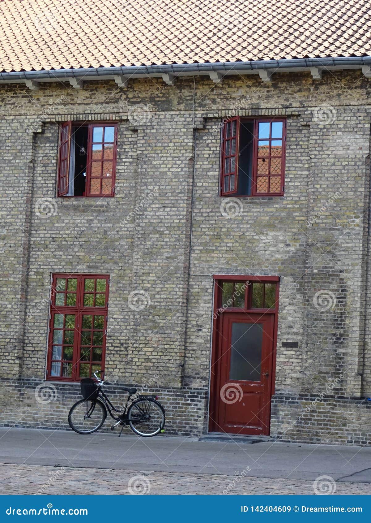 Jechać na rowerze przed starym budynkiem w Kopenhaga, Dani