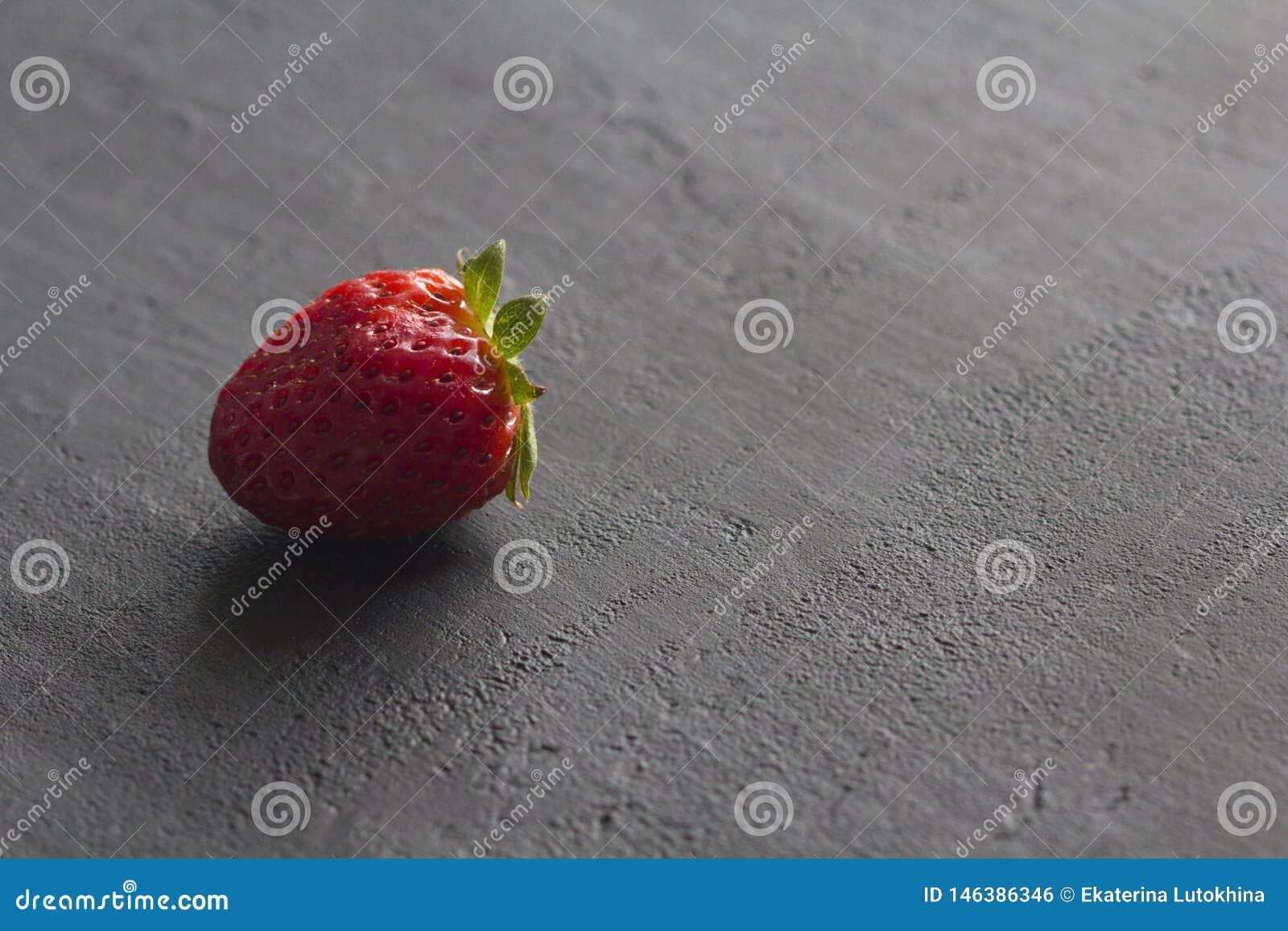 Jeden czerwona pi?kna truskawka w g?r? na czarnym zmroku betonu tle, minimalista Boczny widok, kopii przestrze? dla tw?j teksta M